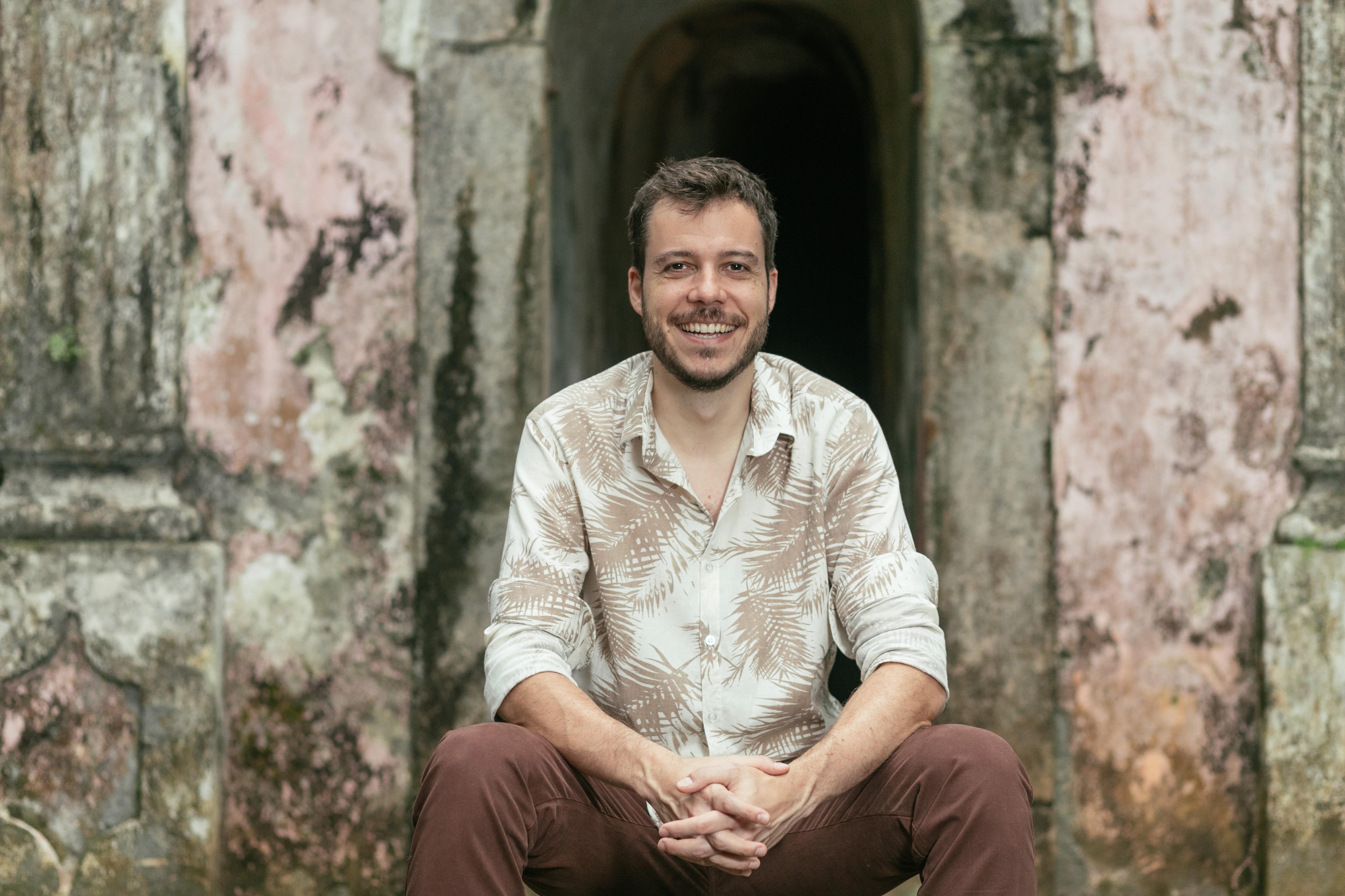 João Cavalcanti sentado na escadinha em frente a uma porta