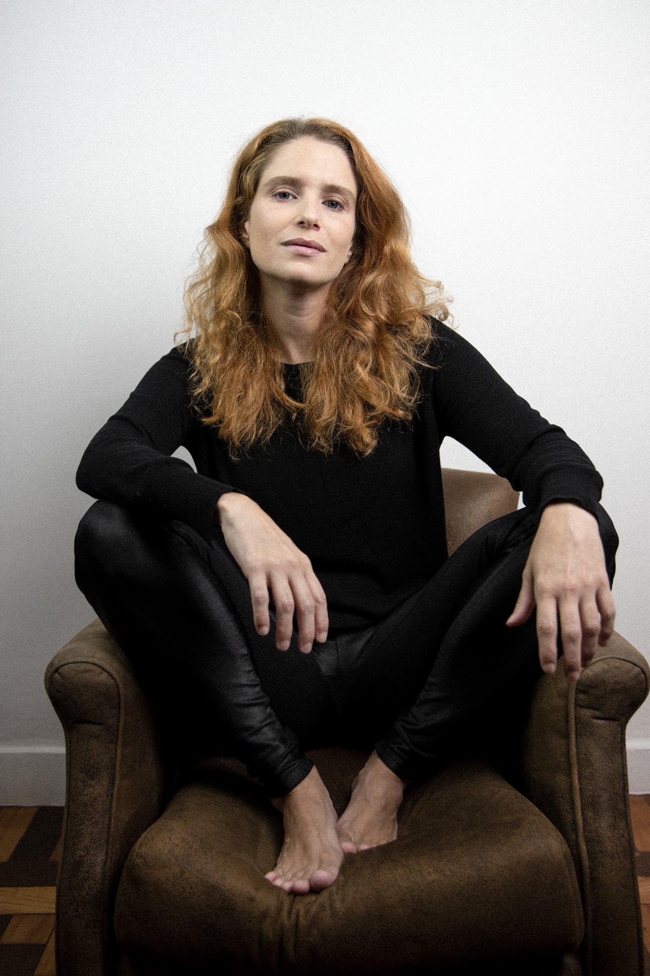 Atriz Julia Lund sentada numa poltrona, com os pés em cima do móvel