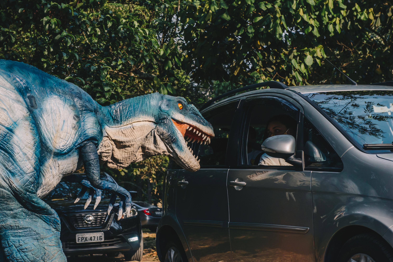 Réplica de tiranossauro rex ao lado de um carro