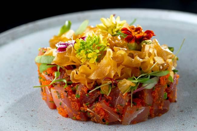 A imagem mostra um tartare de atum coberto de chips de gengibre e flores comestíveis