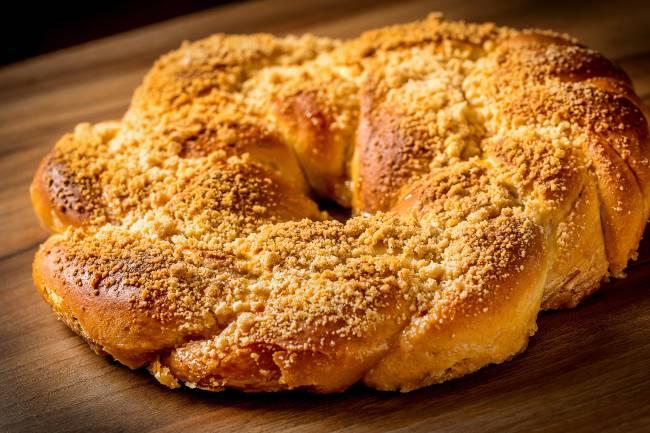 A imagem mostra uma rosca de reis, pão doce redondo coberto de frutas cristalizadas