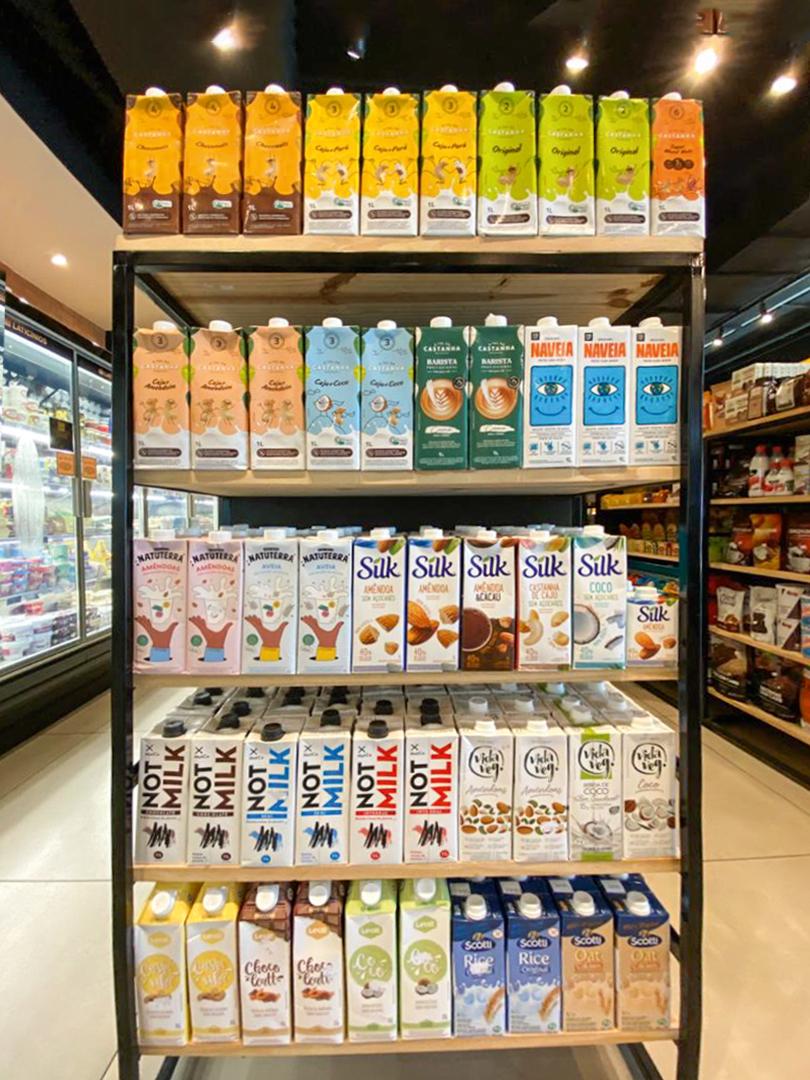 A imagem mostra uma seção de leites vegetais de um mercado com várias marcas disponíveis nas prateleiras