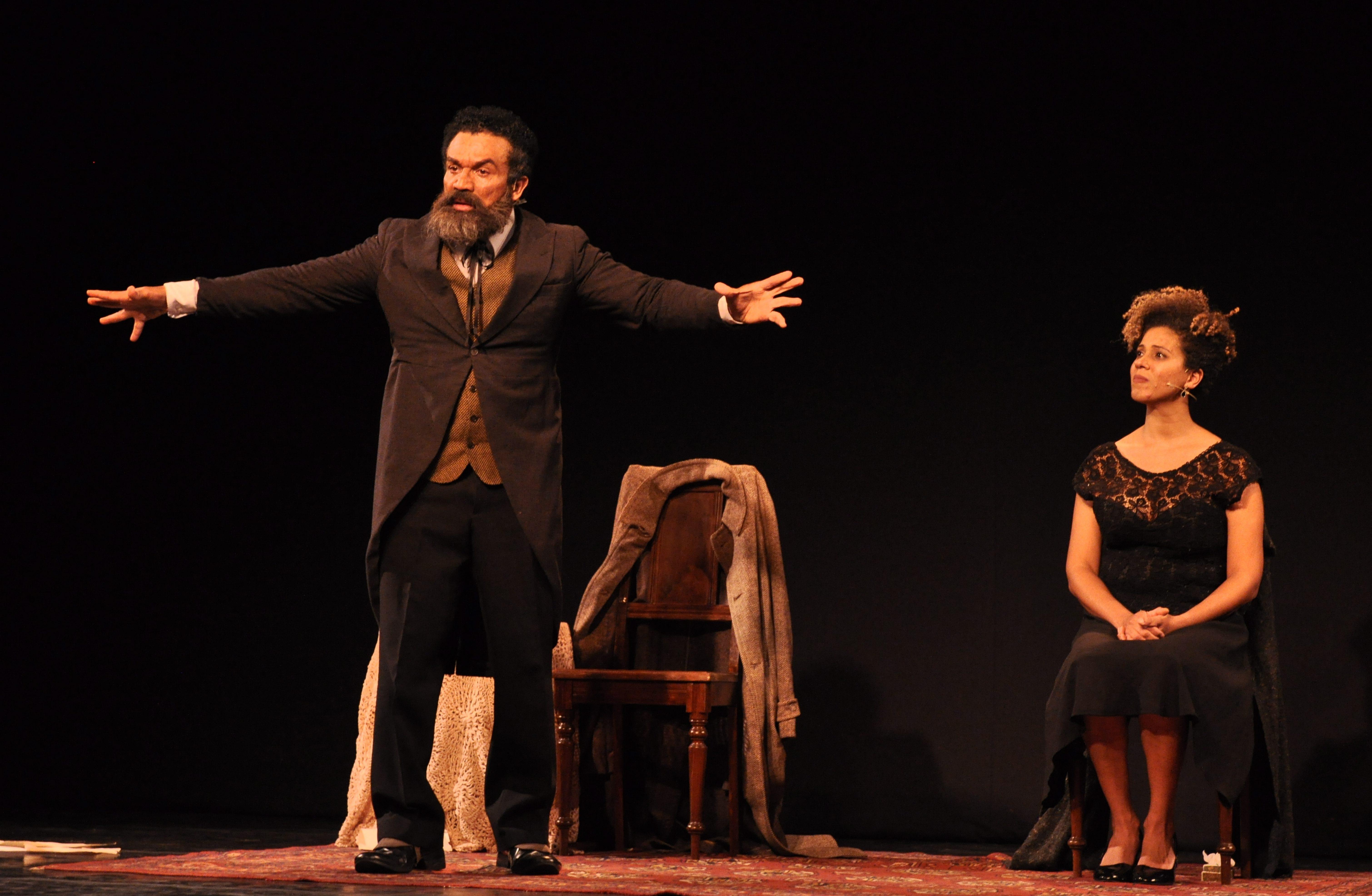 Ator Deo Garcez no palco com os braços abertos e roupas de época. Ao fundo, atriz está sentada