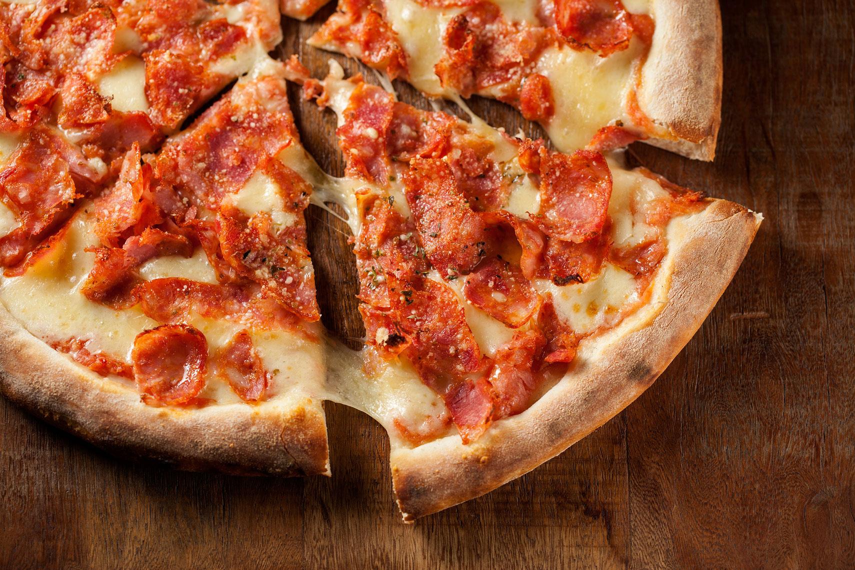A imagem mostra fatias de pizza de calabresa