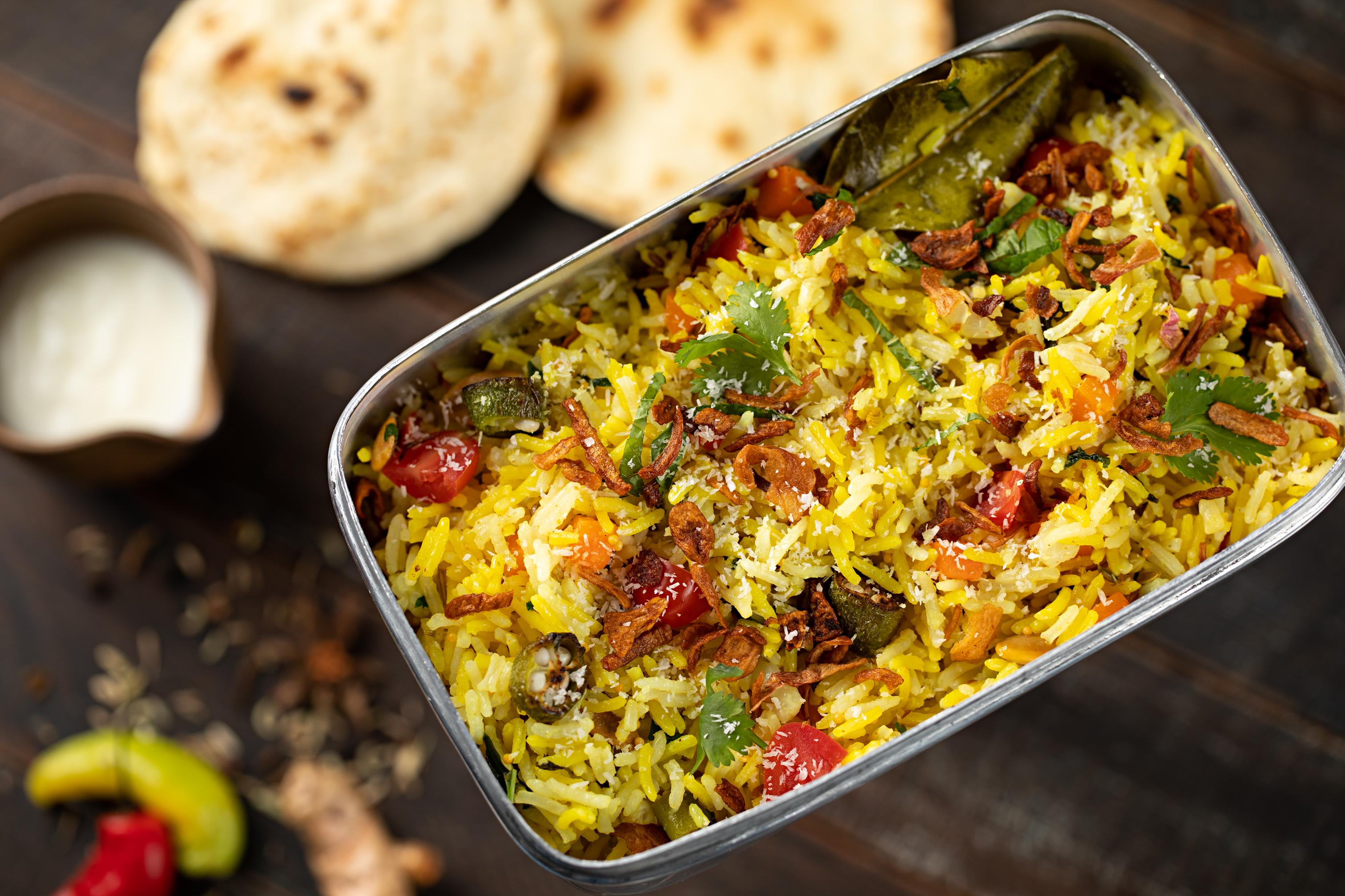 A imagem mostra um tabuleiro cheio de arroz indiano com vegetais