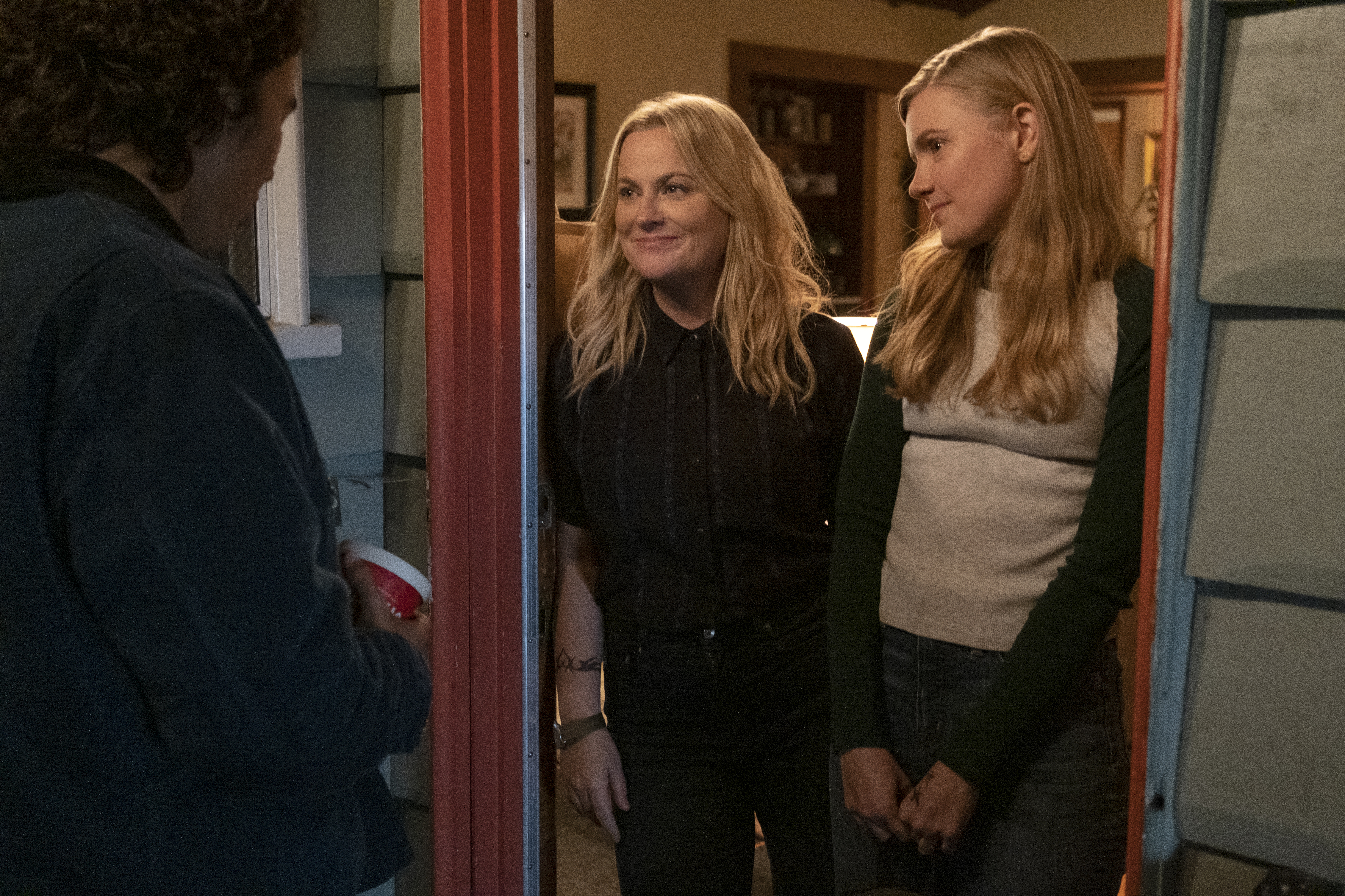 Amy Poehler no batente de uma porta, ao lado da filha, com um homem de costas