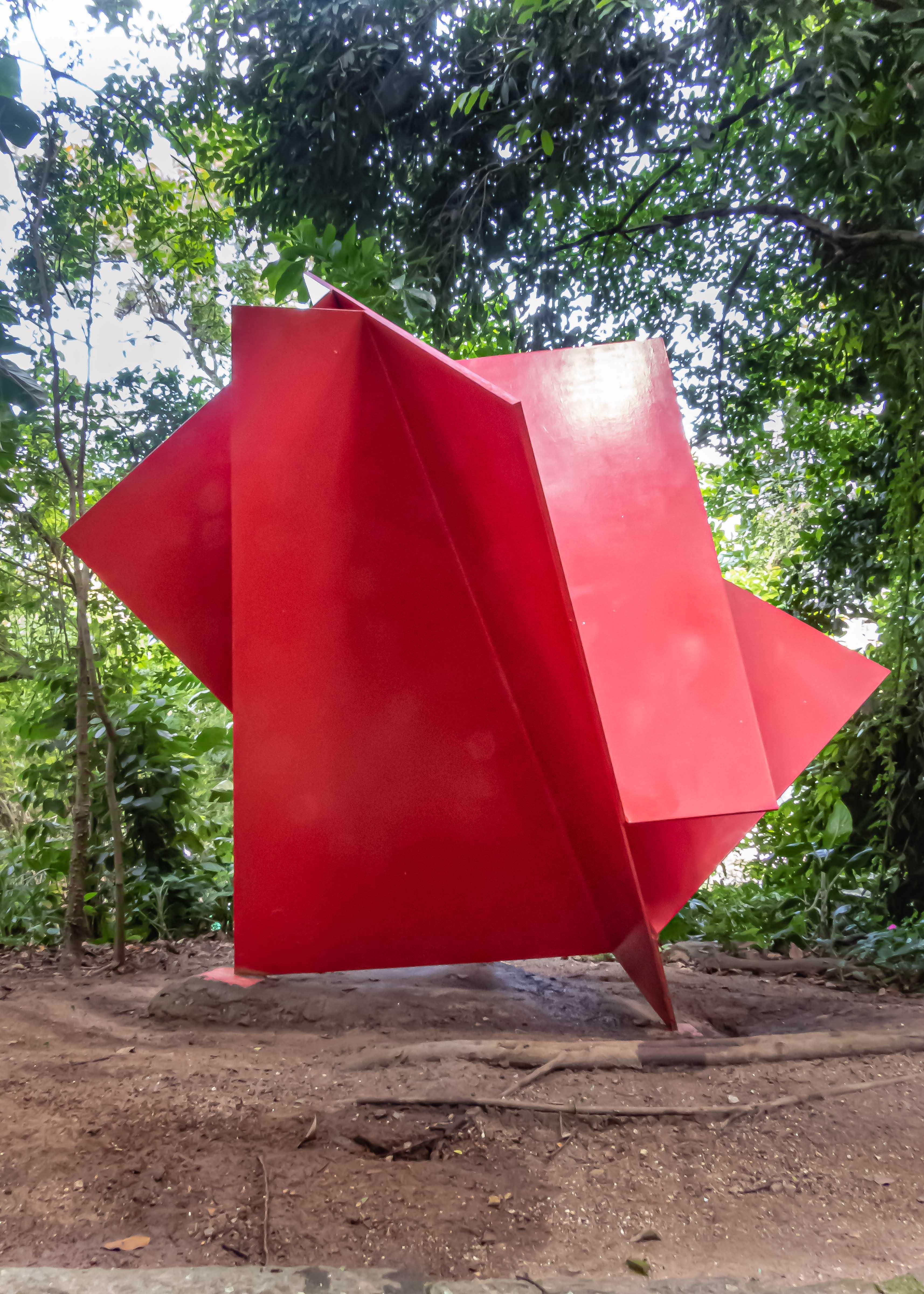 Escultura em formato gigante, com placas vermelhas, num fundo com muitas árvores