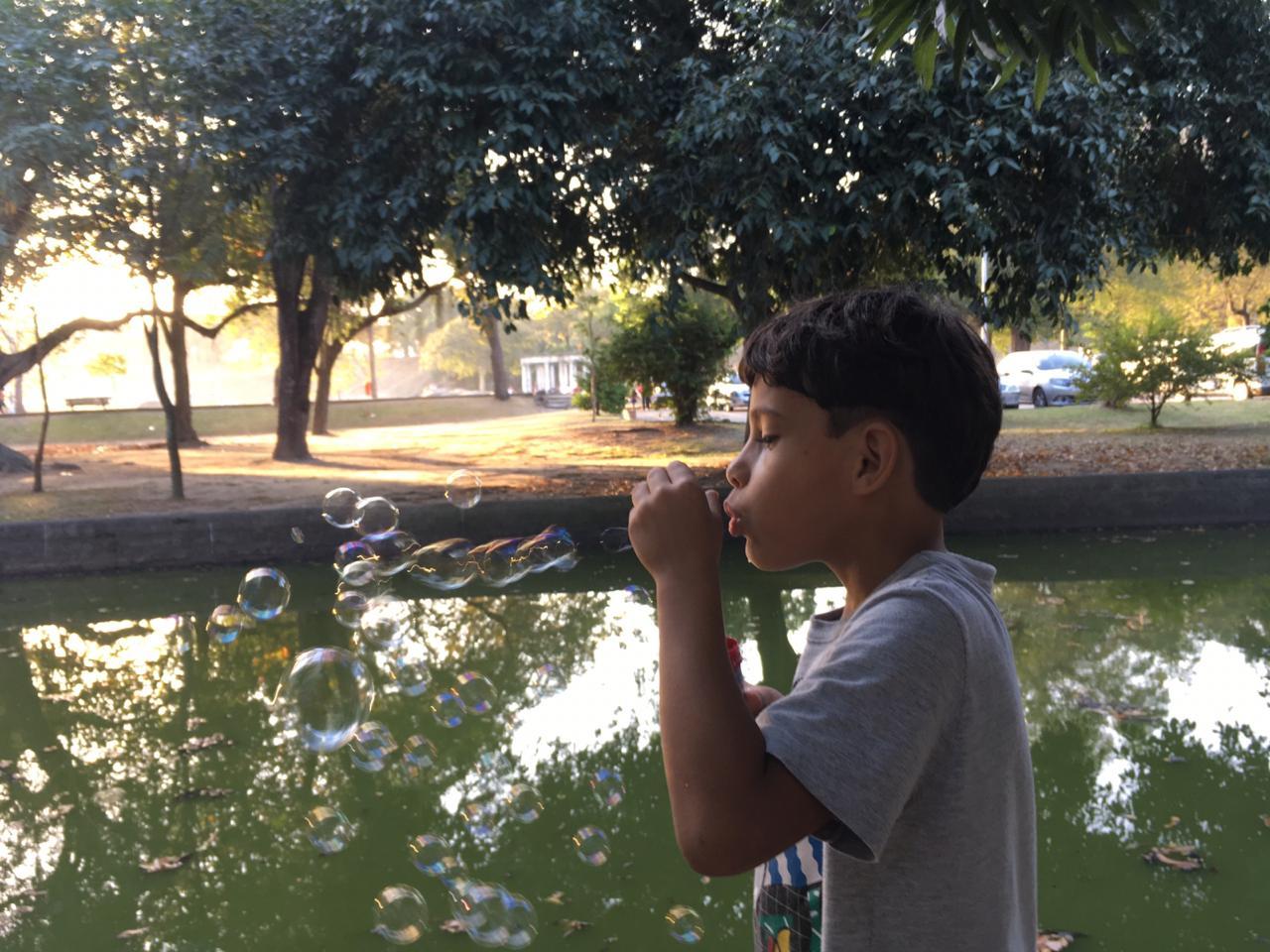 Menino sopra bolhas de sabão em frente a um lago