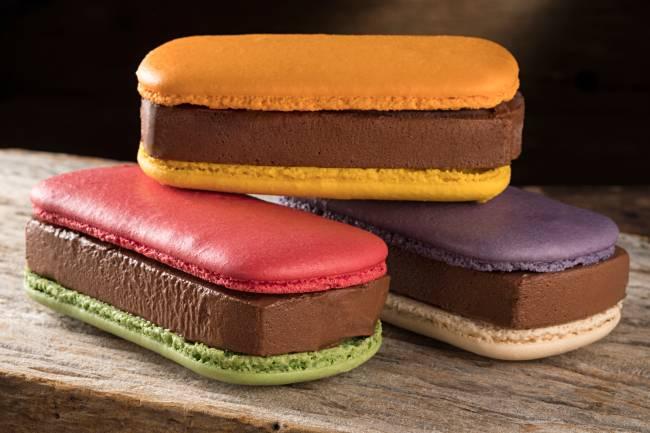 A imagem mostra três sanduíches coloridos com macaron e recheio de sorvete