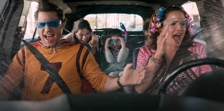 Atores num carro, com crianças gritando e pais desesperados