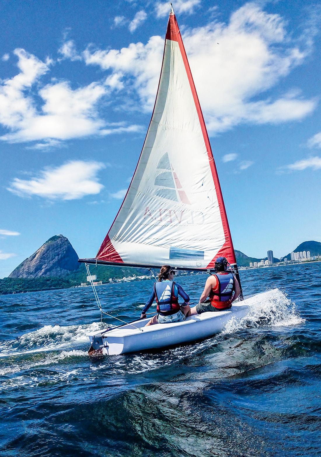 A imagem mostra duas pessoa num dingue, barco a vela, nas águas da Baía de Guanabara