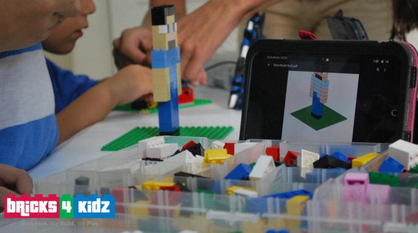 Crianças montam peças de lego e há uma tela em cima da mesa