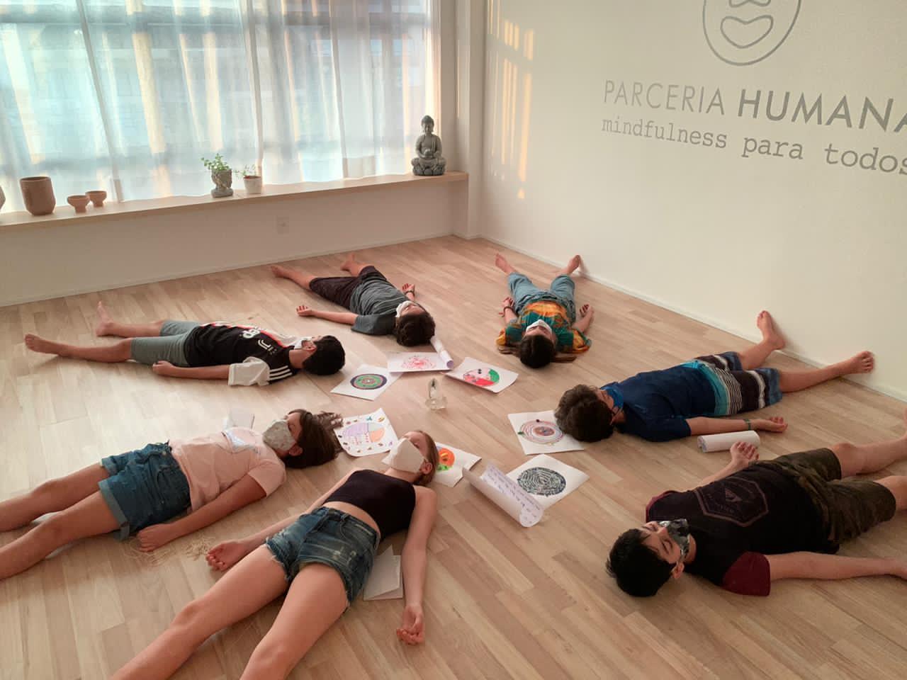 Crianças deitadas no chão, em círculo, com papéis desenhados também no chão