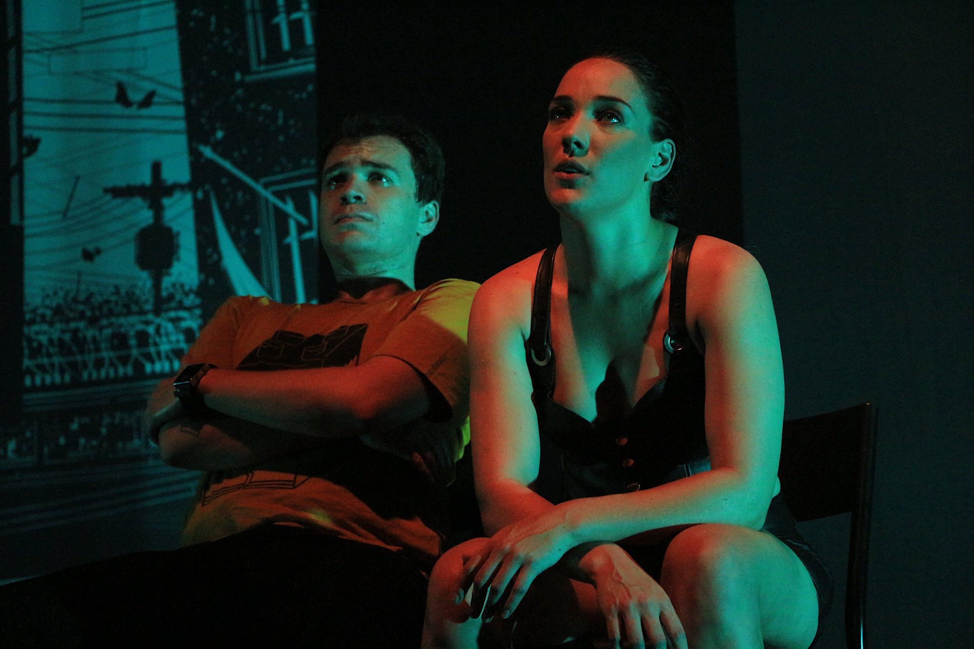 Atores sentados no palco, com uma luz esverdeada e avermelhada