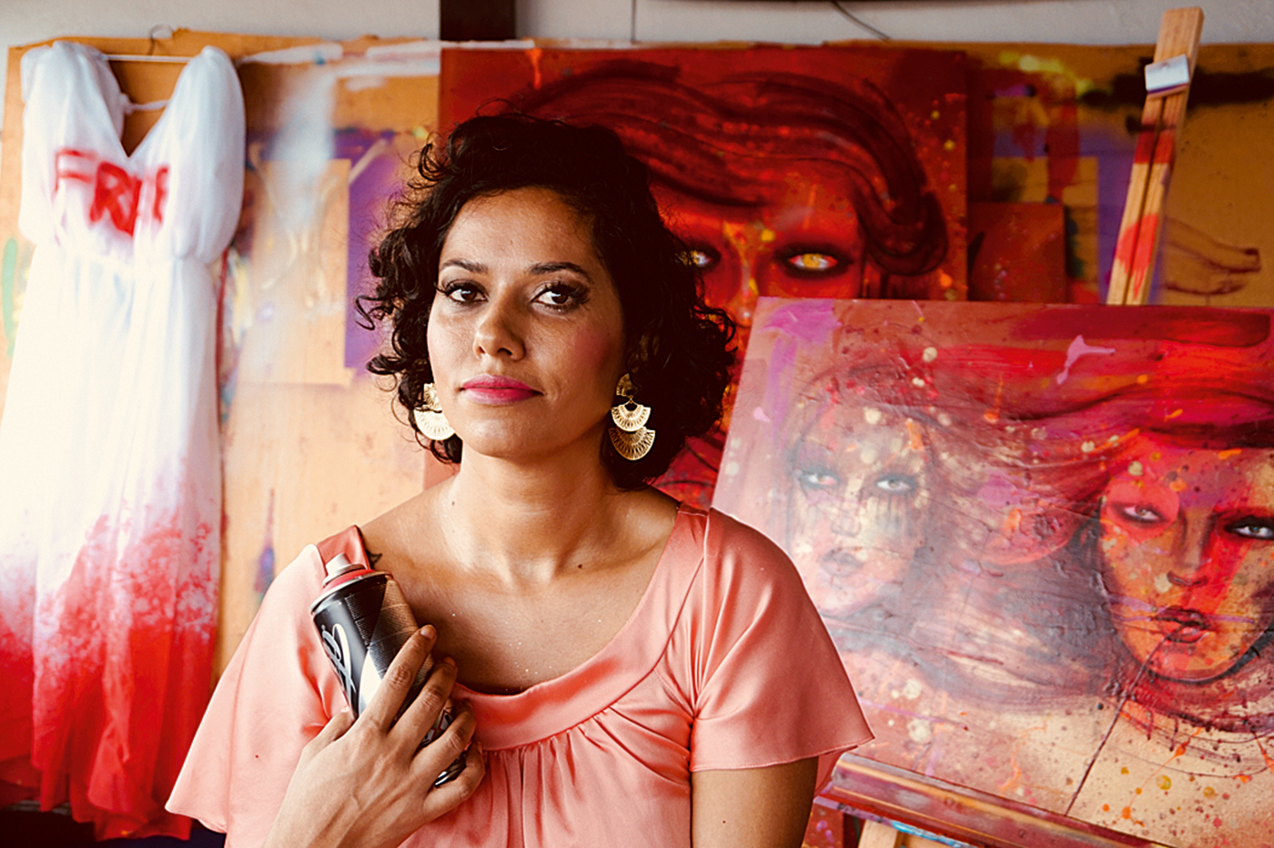 A imagem mostra a artista Panmela Catsri à frente de um de seus trabalhos, com uma lata de tinta em spray na mão