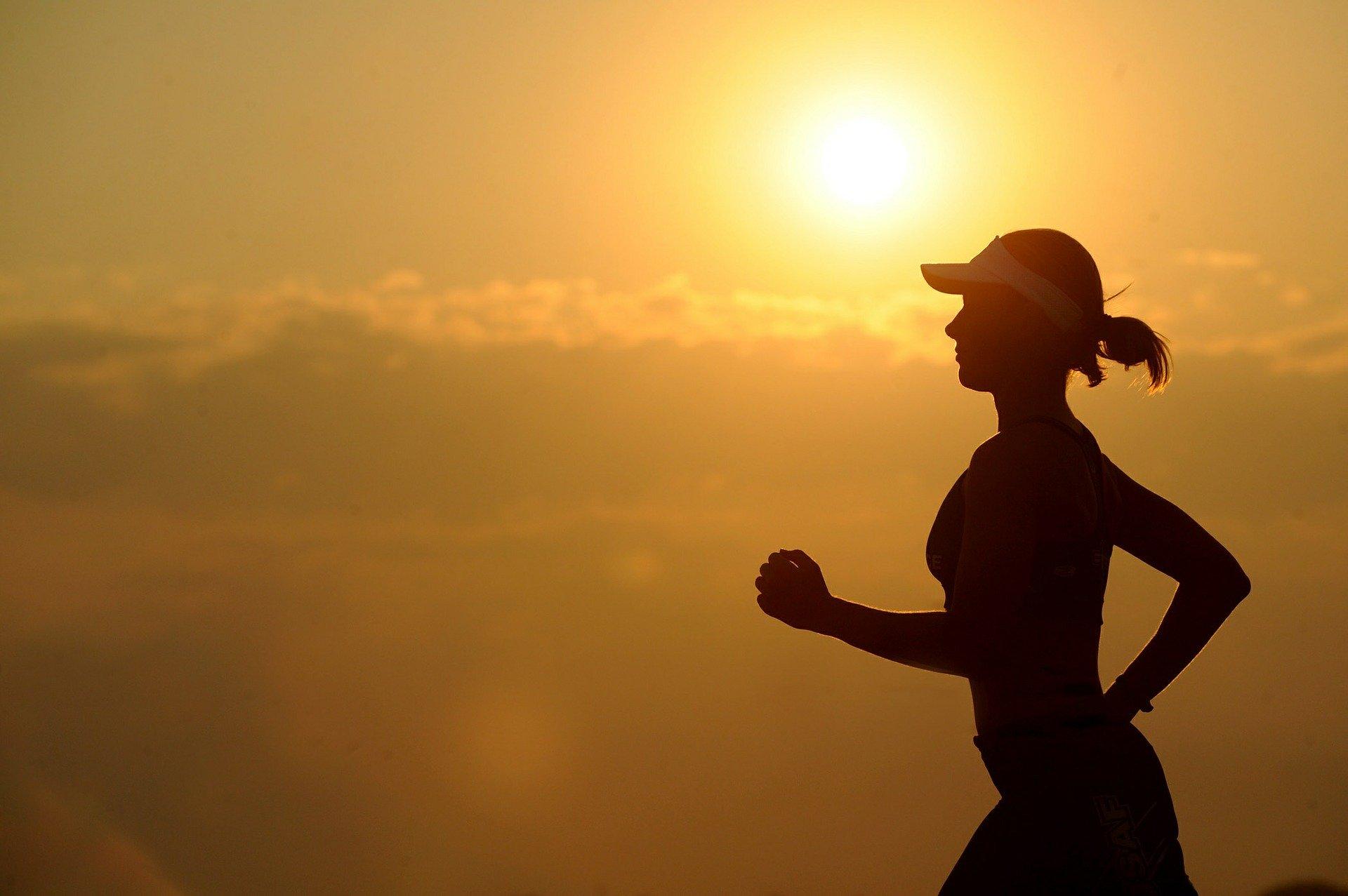 Mulher pratica corrida ao nascer do sol.