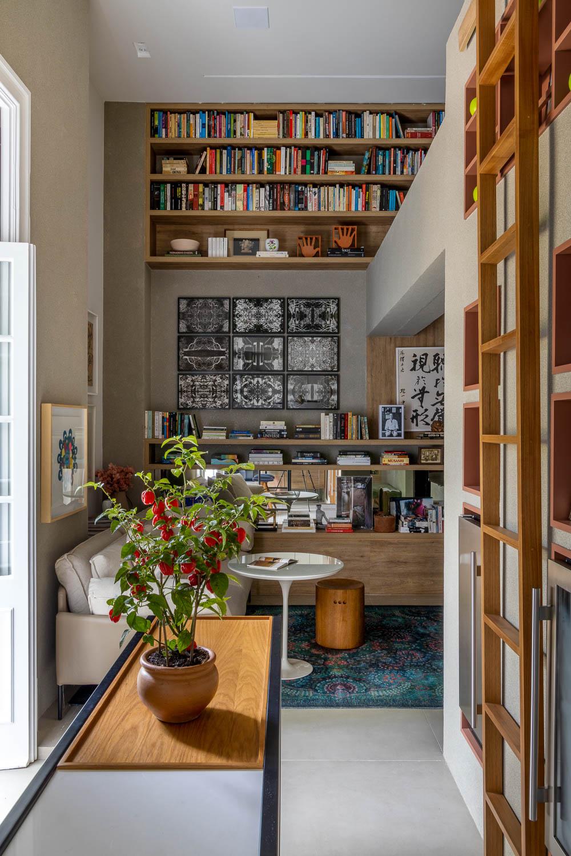 Sala de estar com bar e cozinha, com uma prateleira ao fundo e muitos livros