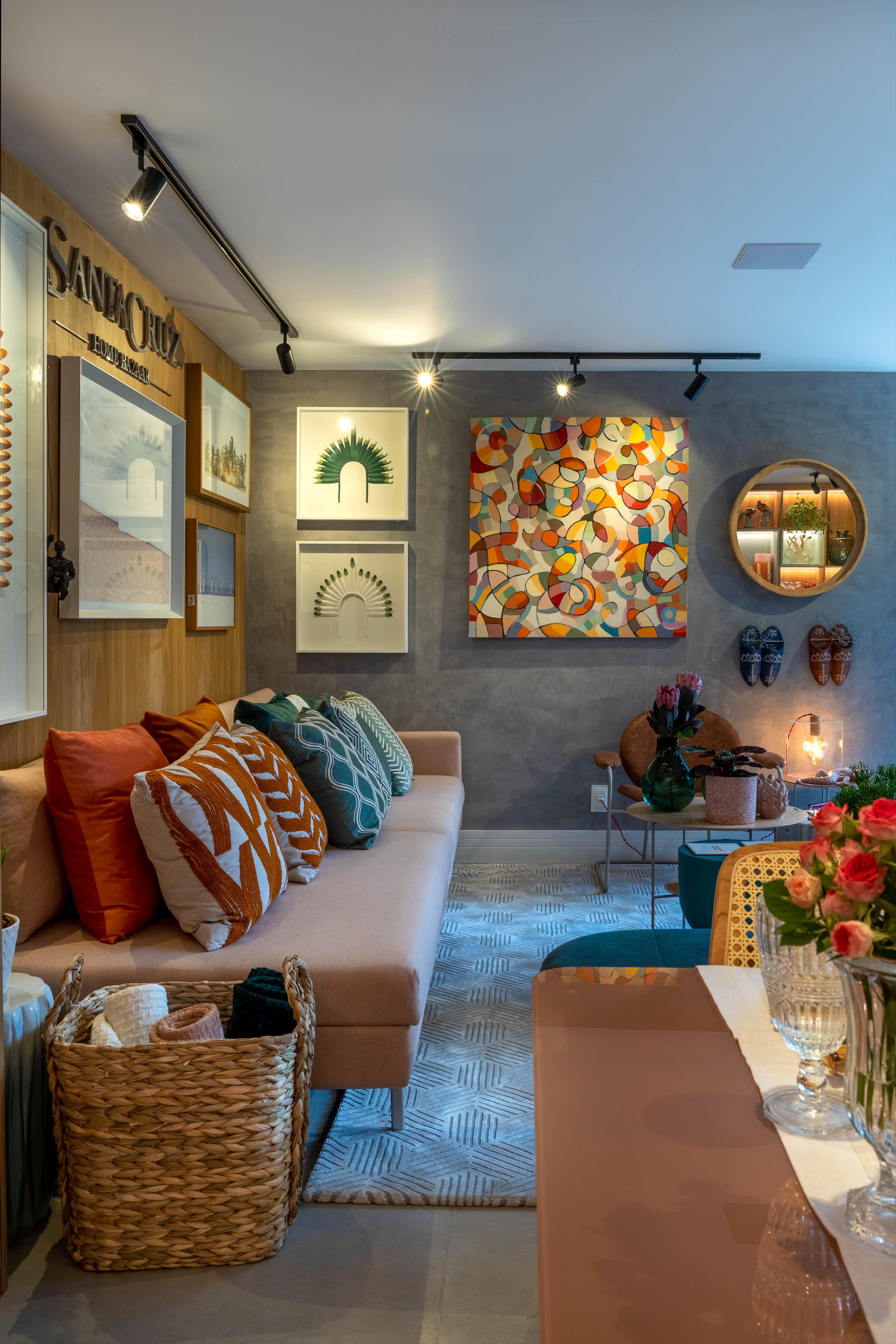 Sala de estar com quadros coloridos, sofás em tons de rosa e almofadas coloridas