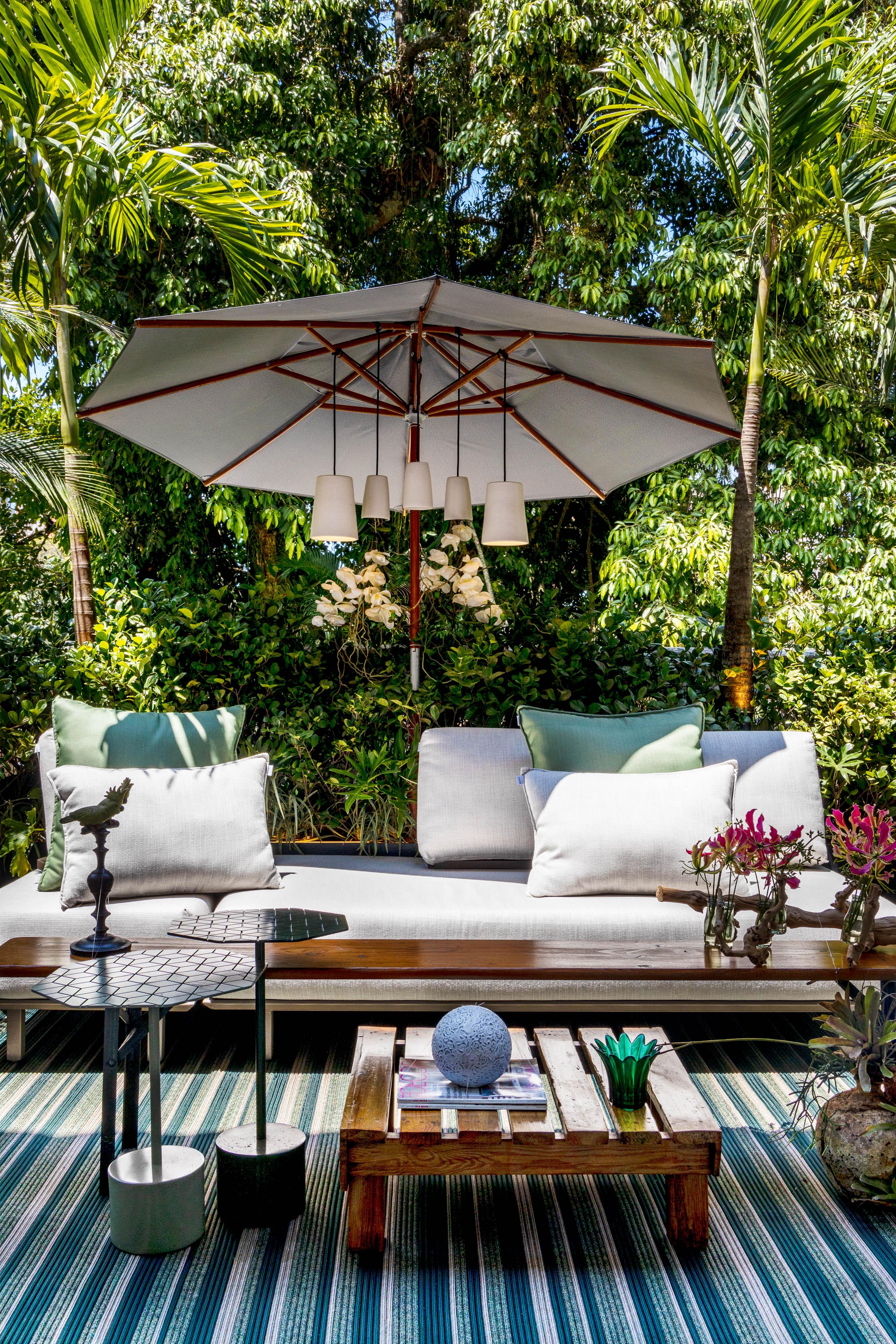 Varanda da Casacor de 2021 com um grande sofá e ombrelone