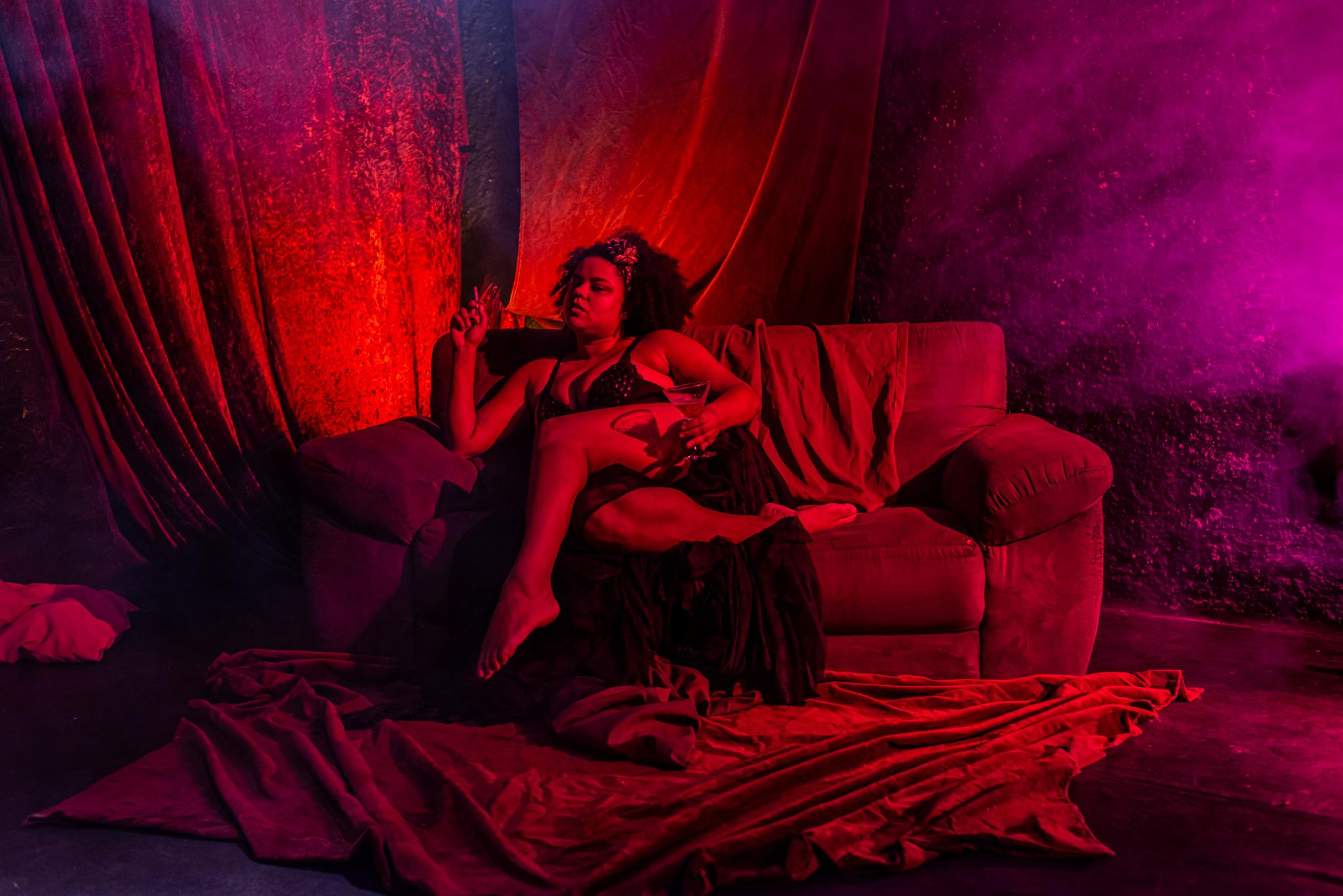 Atriz com roupa íntima sentada num sofá, sob luz vermelha