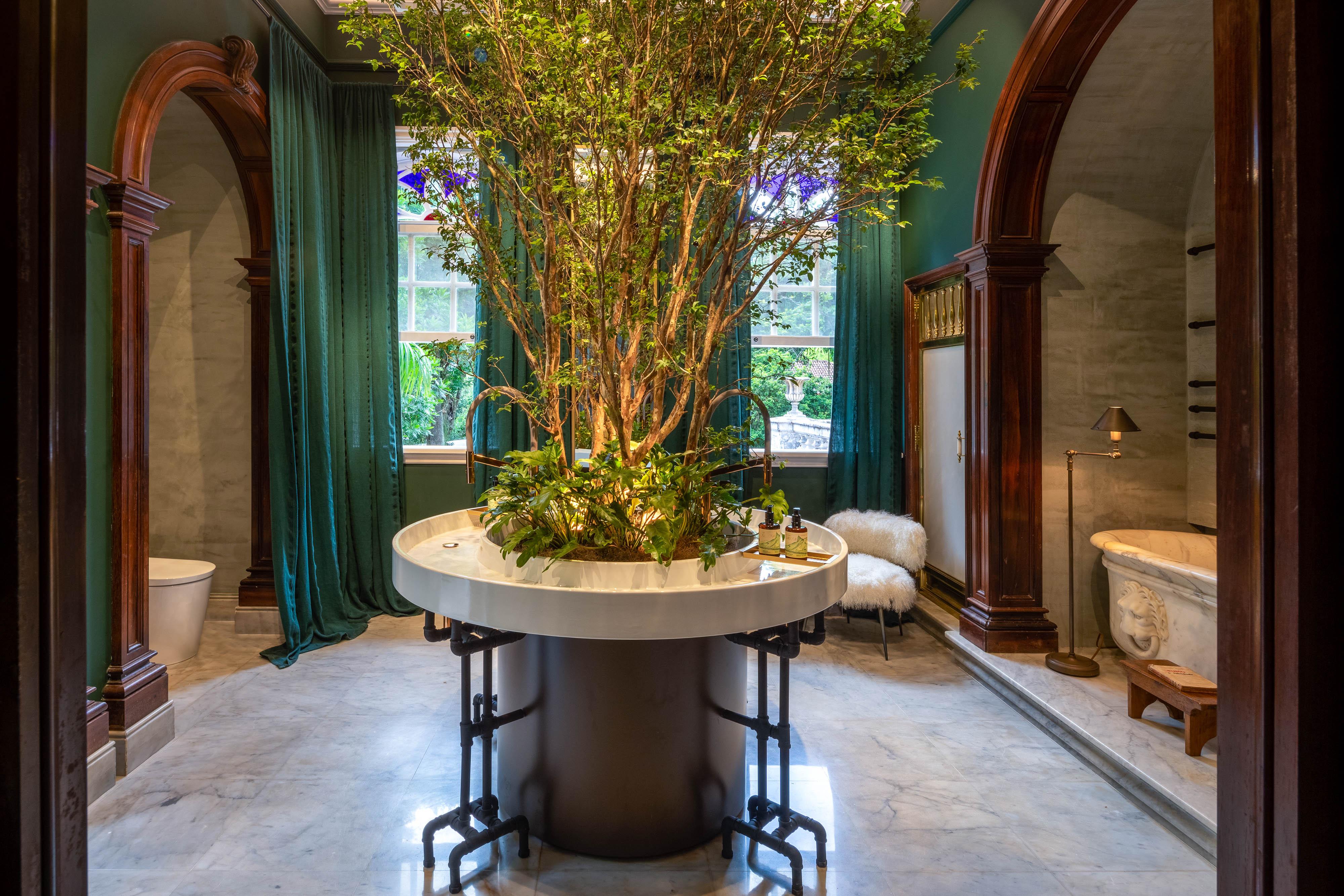 Banheiro da Casacor Rio 2021 tem mesa no centro com espécie de árvore dentro dela