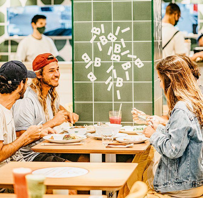 Lanchonete Bibi Sucos com clientes sorrindo e comendo nas mesas