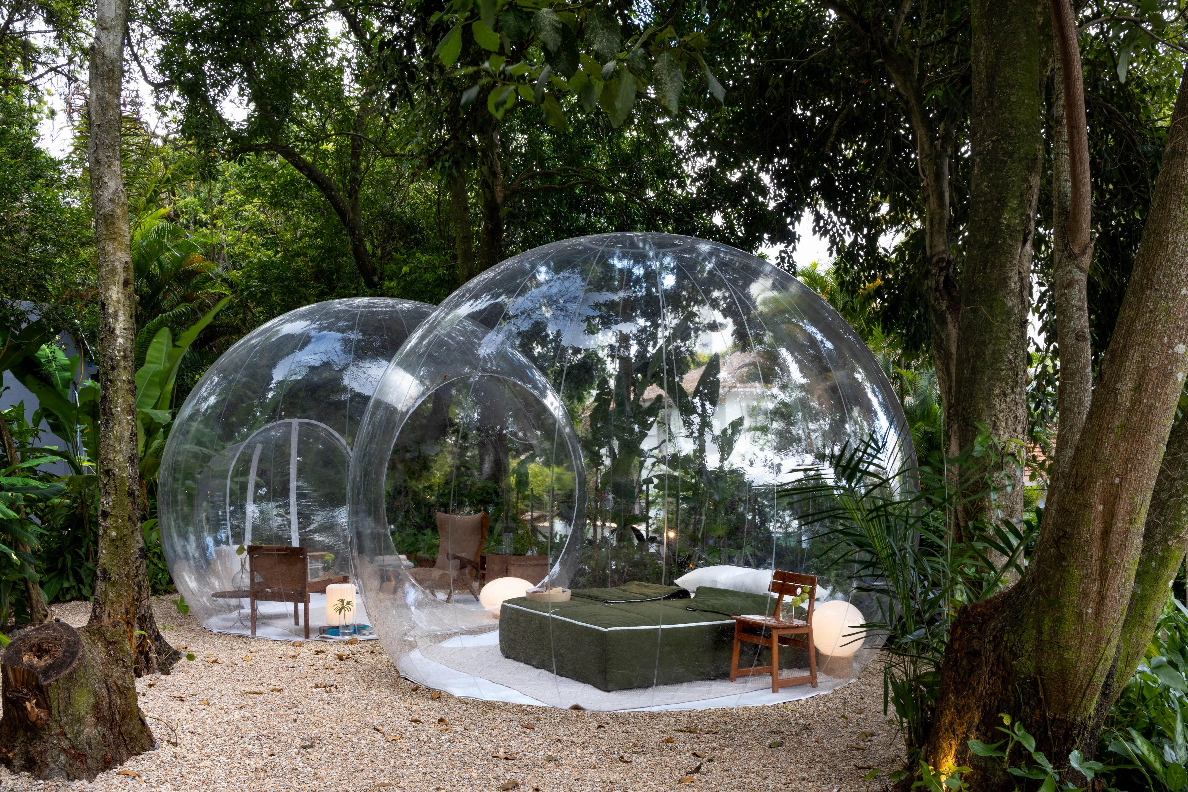 Bolha gigante no meio do jardim com cama e poltronas dentro dela