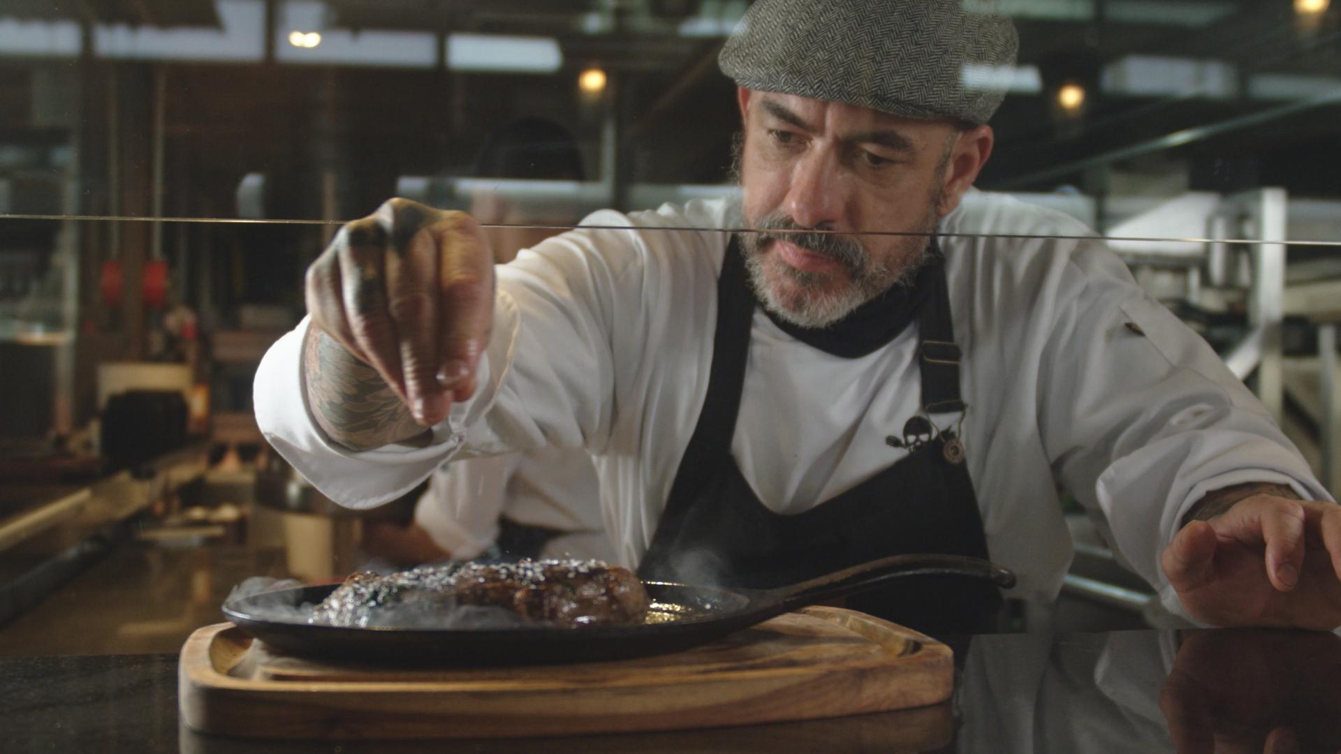 Chef Henrique Fogaça temperando uma carne