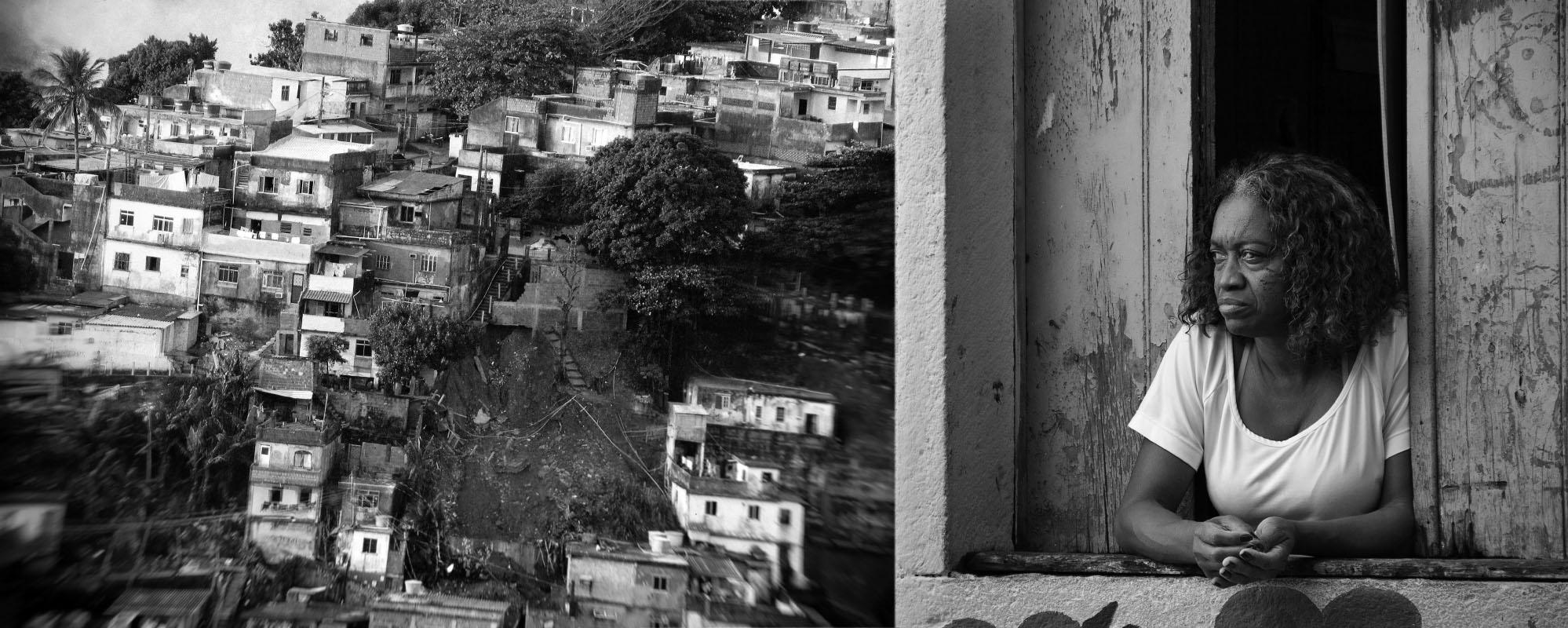 Senhora apoiada na janela de um casa numa favela