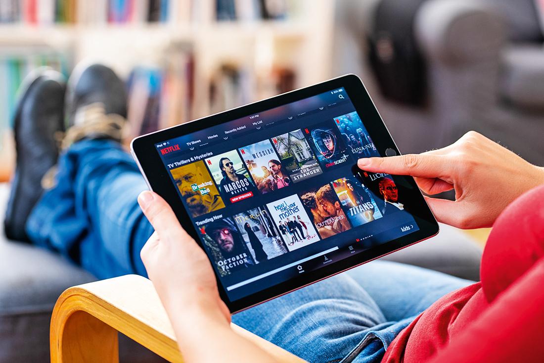 Pessoa segurando um tablet com o app da Netflix