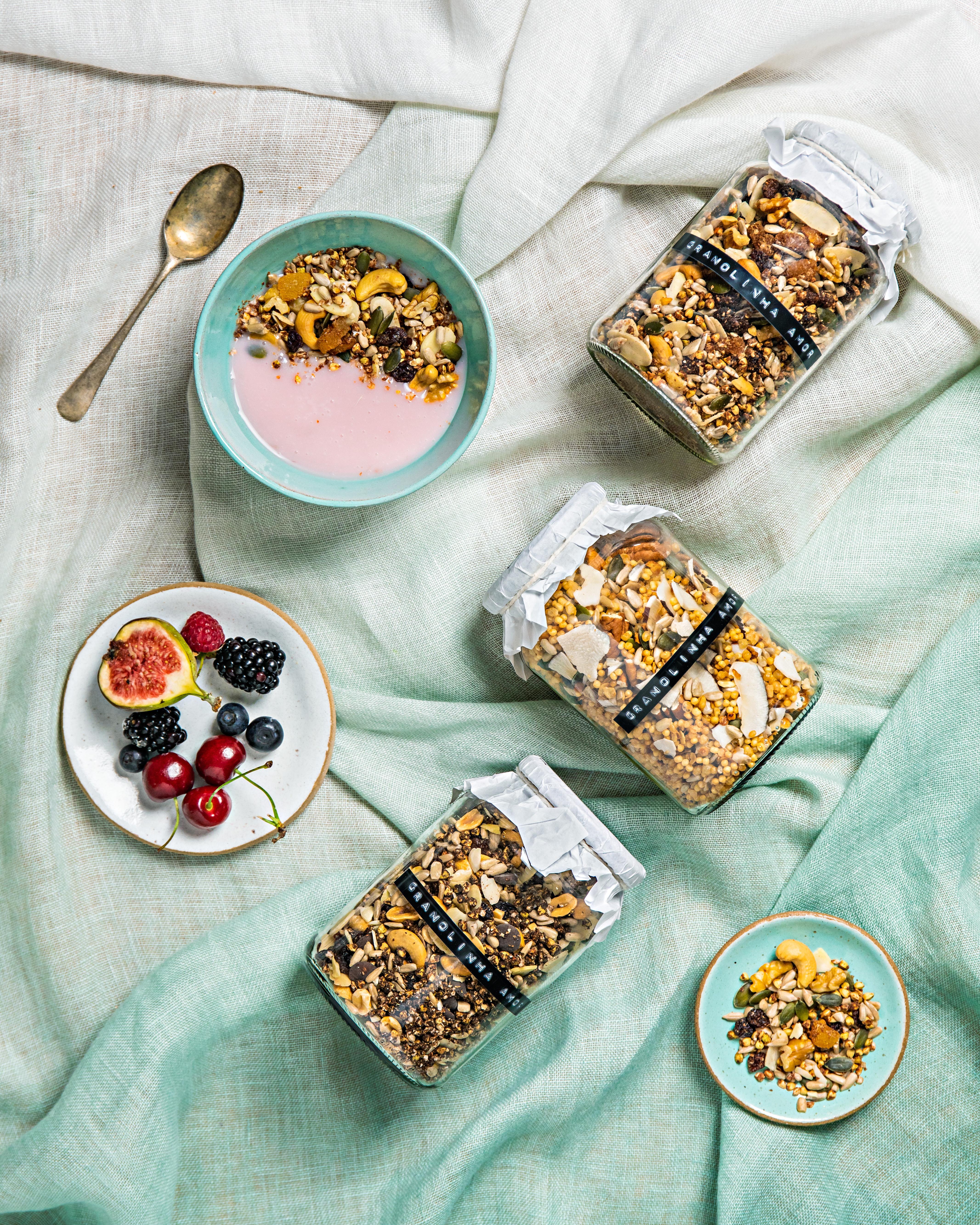 várias granolas com pote de frutas