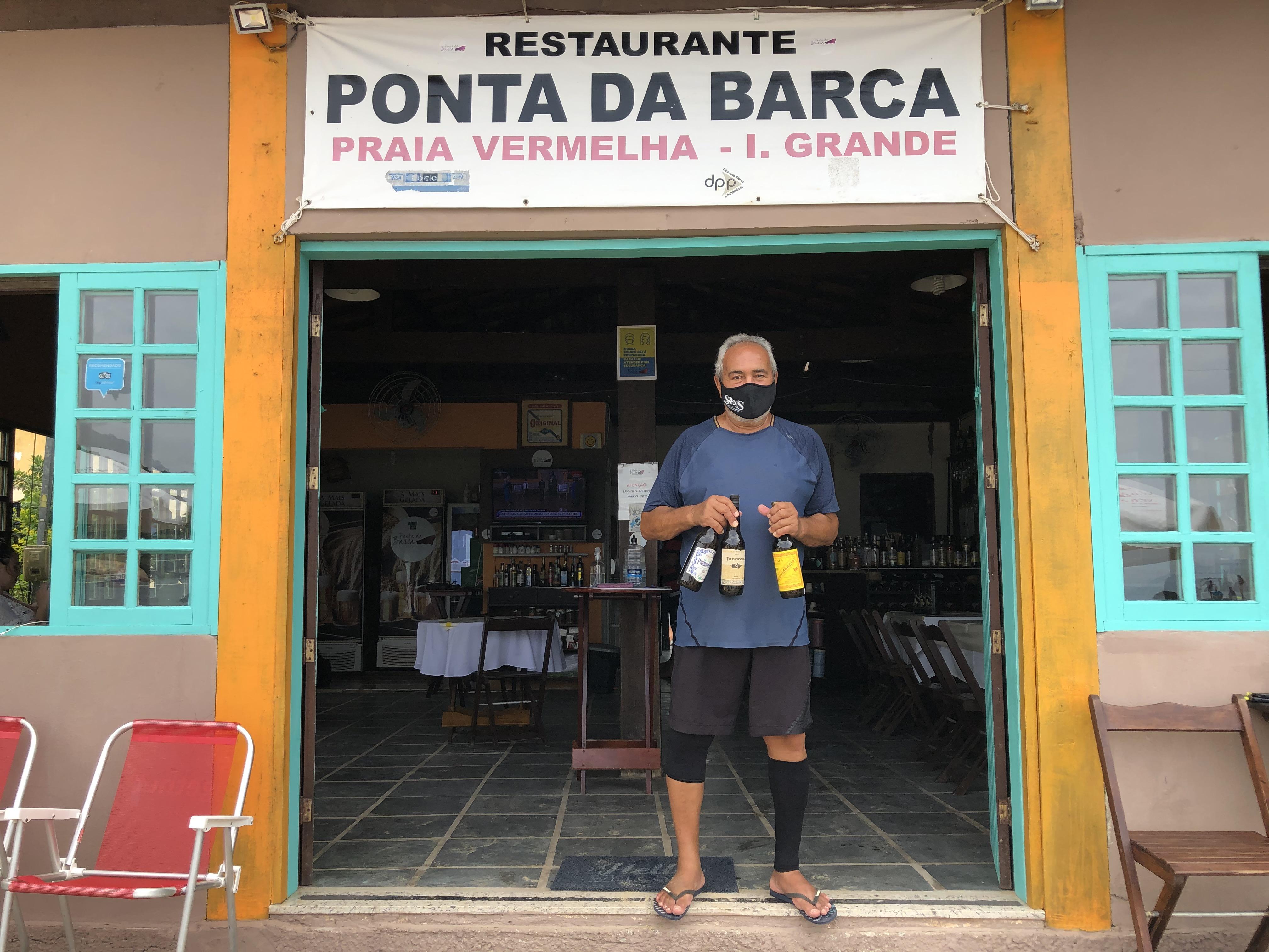 Fernando, dono do Ponta da Barca, posa com suas cachaças artesanais