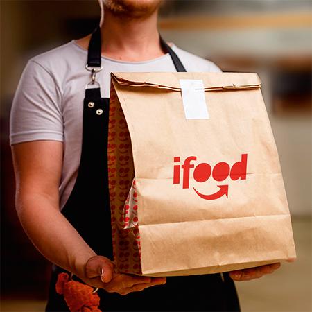 pessoa segurando uma embalagem de entrega do iFood