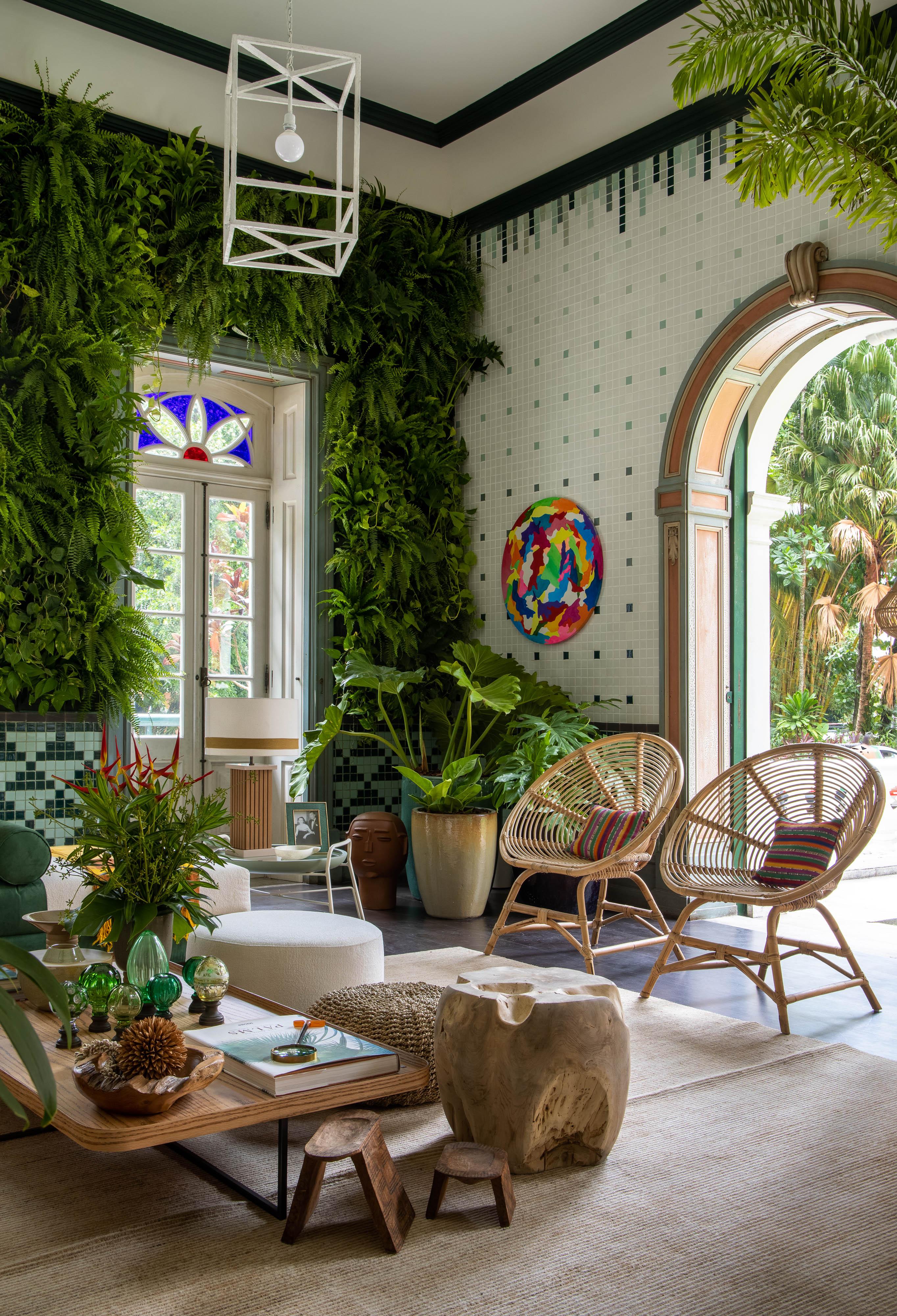 Jardim de inverno com parende de plantas e móveis em tons de bege