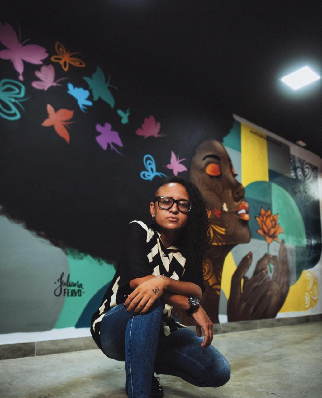 Mulher posa em frente a mural grafitado