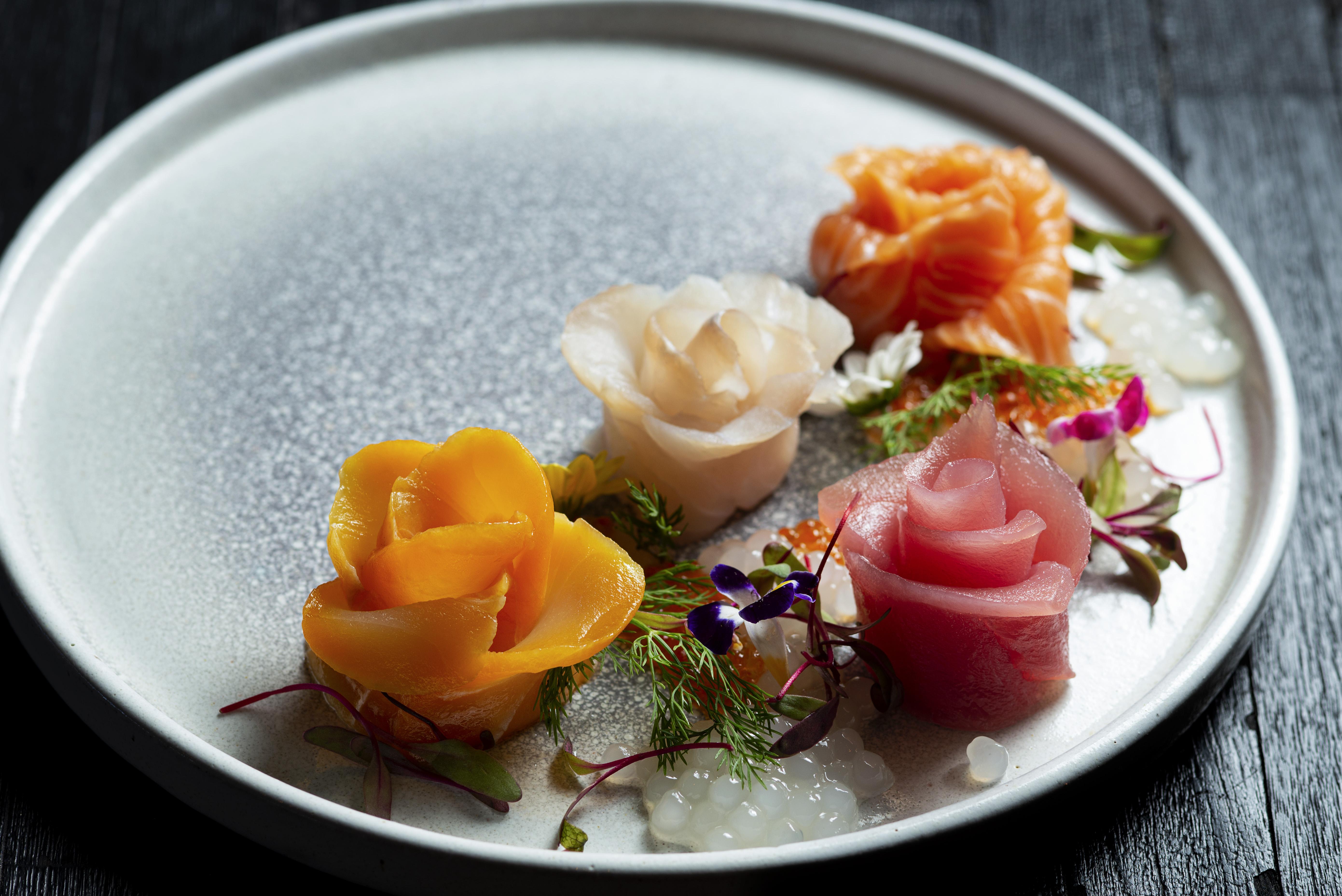 A imagem mostra uma seleção de sashimis em forma de flor