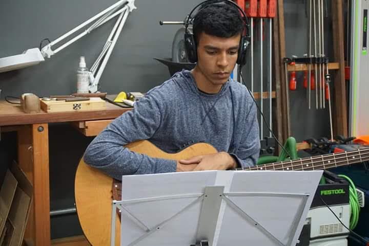 A imagem mostra um músico tocando violão