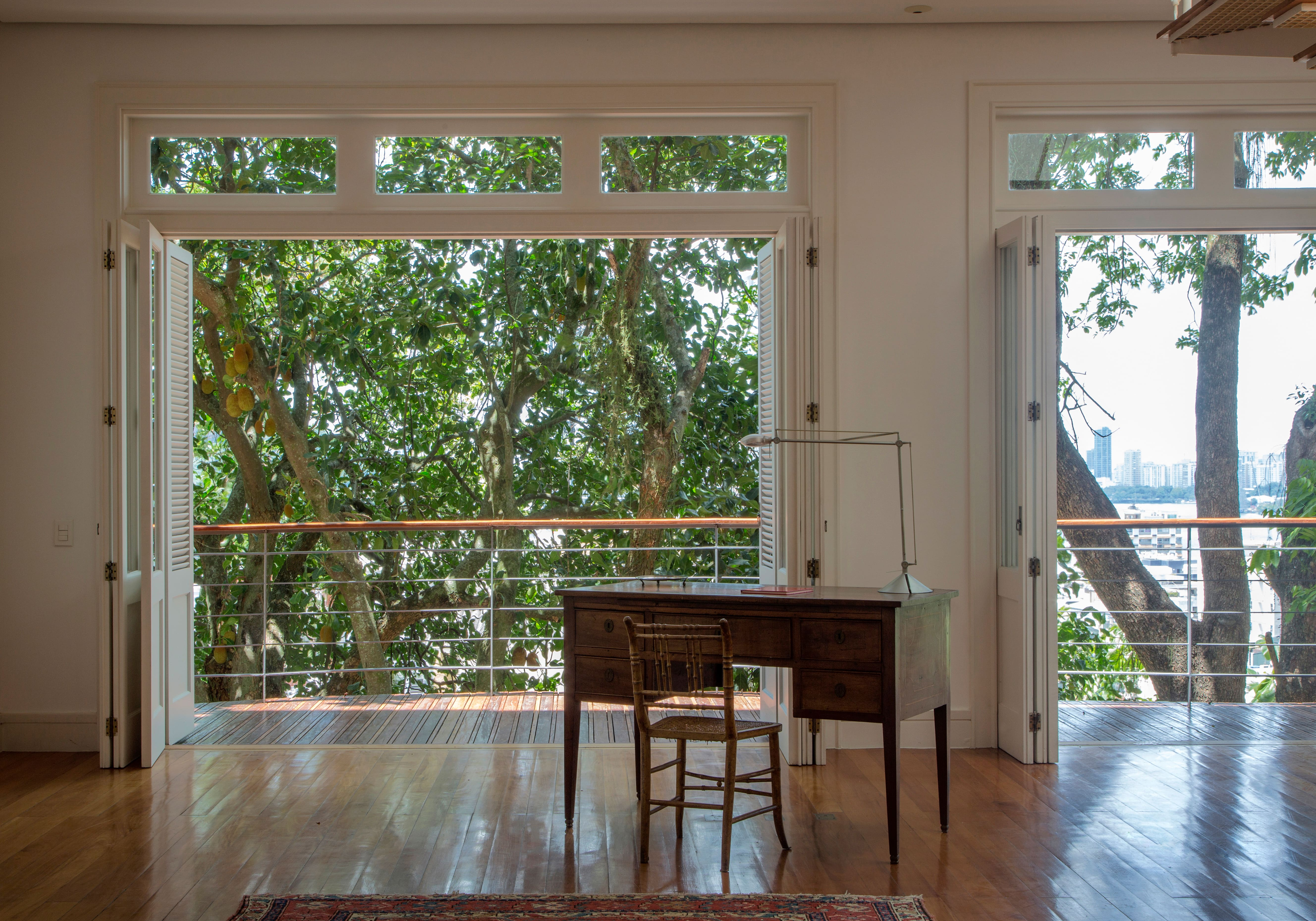 imagem mostra uma escrivaninha na sala com luz natural e janelas