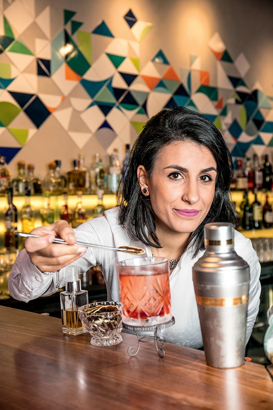 Jéssica Sanchez prepara drinques no balcão com fundo colorido