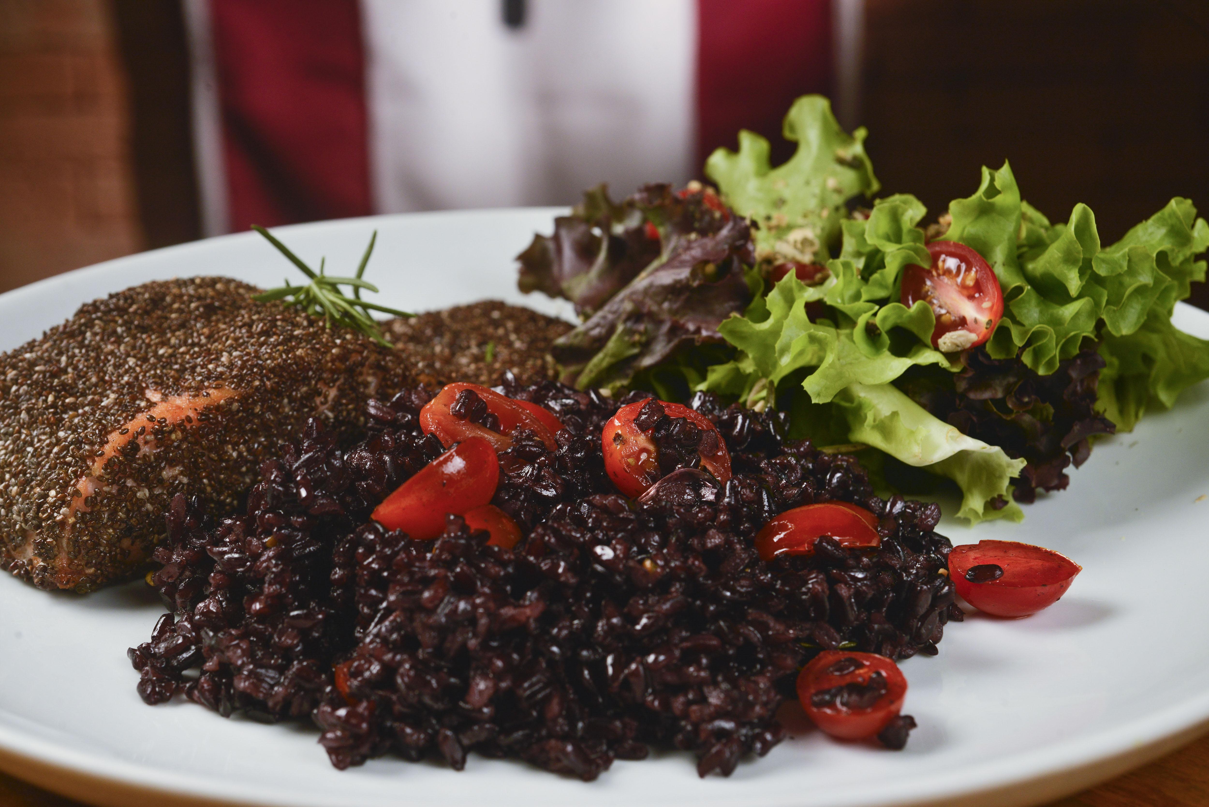 A imagem mostra um prato de salmão em crosta de chia com arroz negro