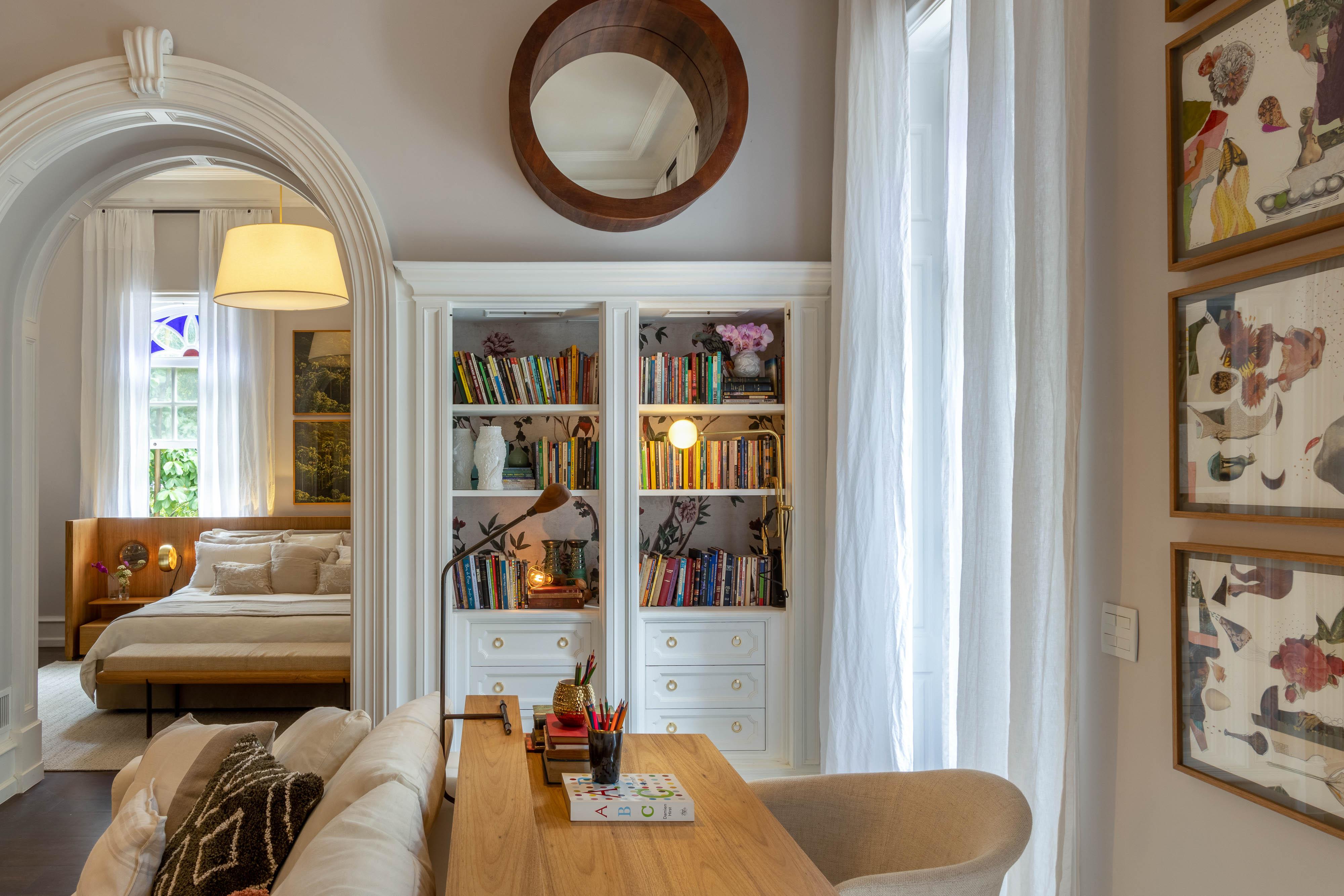 Quarto com prateleira com livros, escrivaninha, sofá e cama ao fundo
