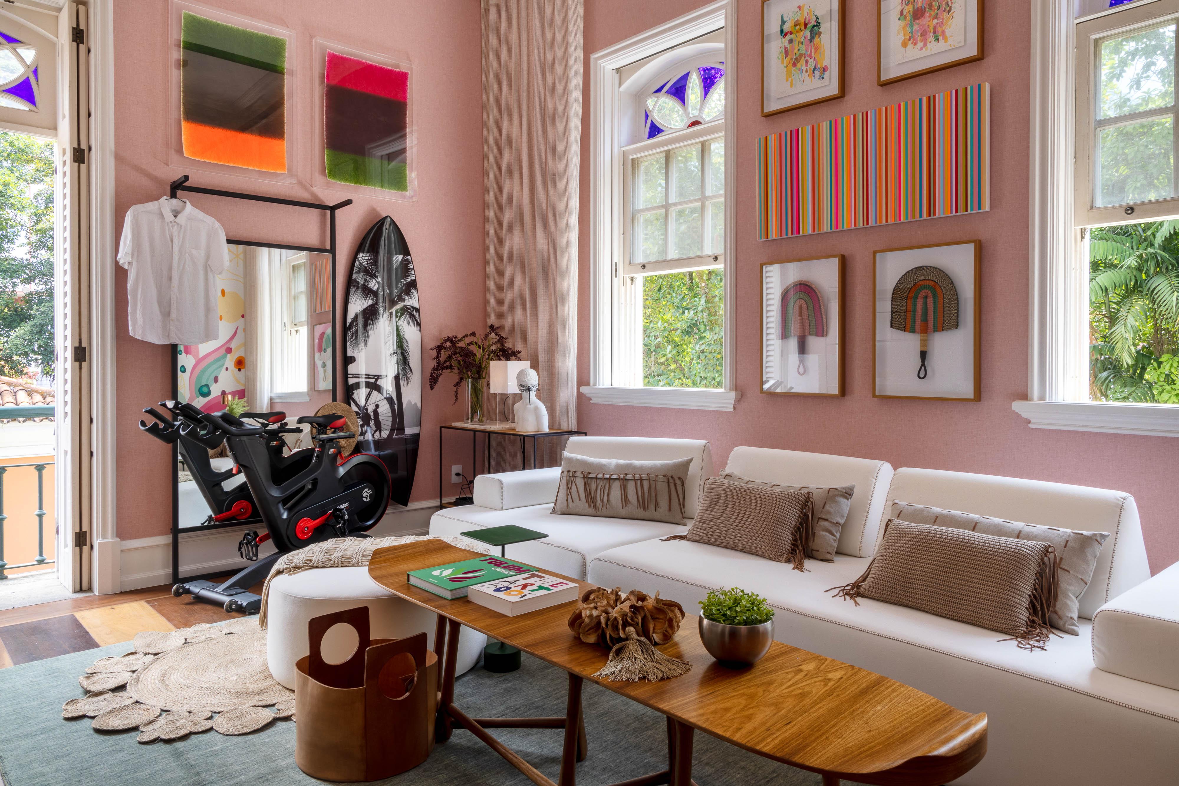 Saleta de estar em tons de rosa, quadros coloridos e uma bicicleta ergométrica