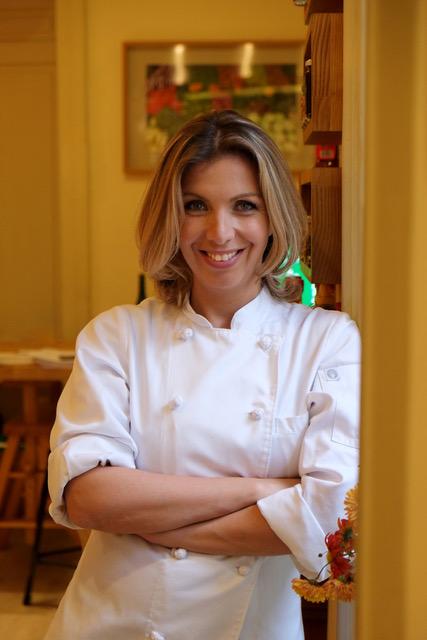 A imagem mostra uma chef de cozinha de braços cruzados
