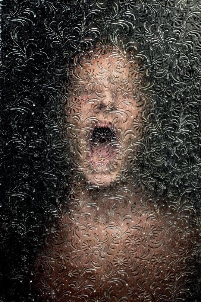 fotografia de mulher gritando sob tela de vidro trabalhada com motivos florais