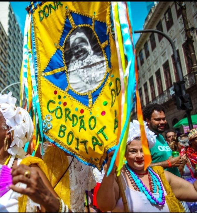 Bloco de Carnaval com estandarte amarelo do bloco Cordão do Boitatá em destaque