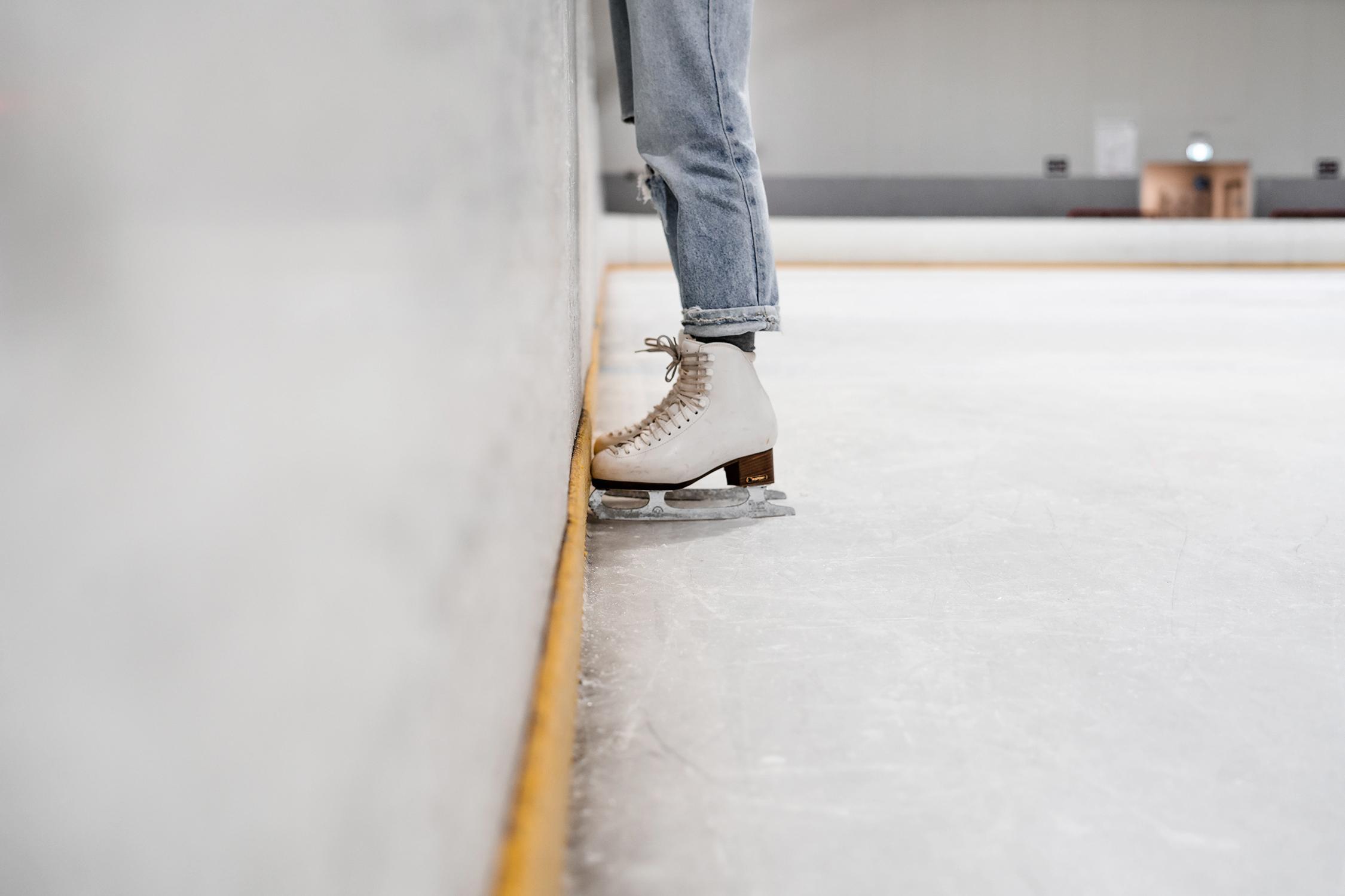 Pernas com patins numa pista de patinação no gelo