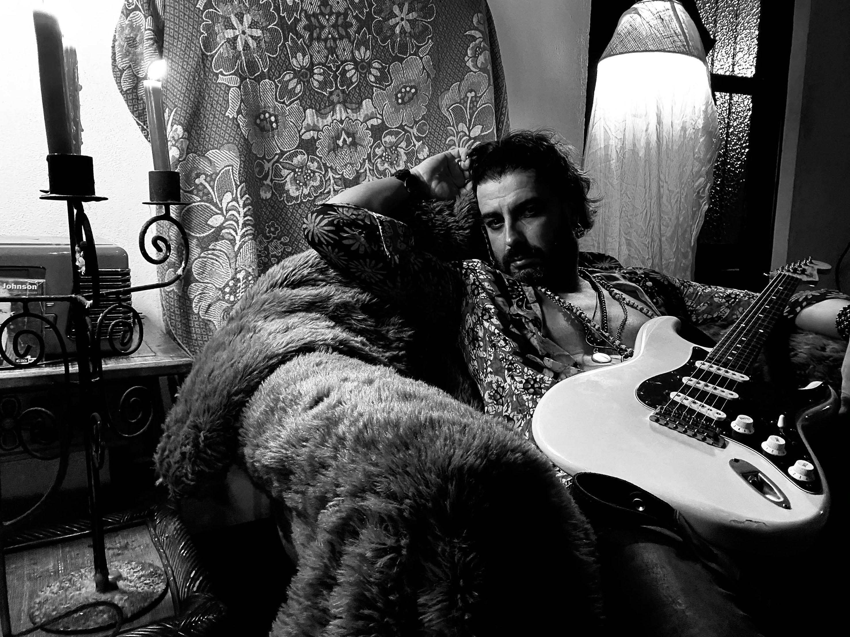 Homem está sentado e segura guitarra