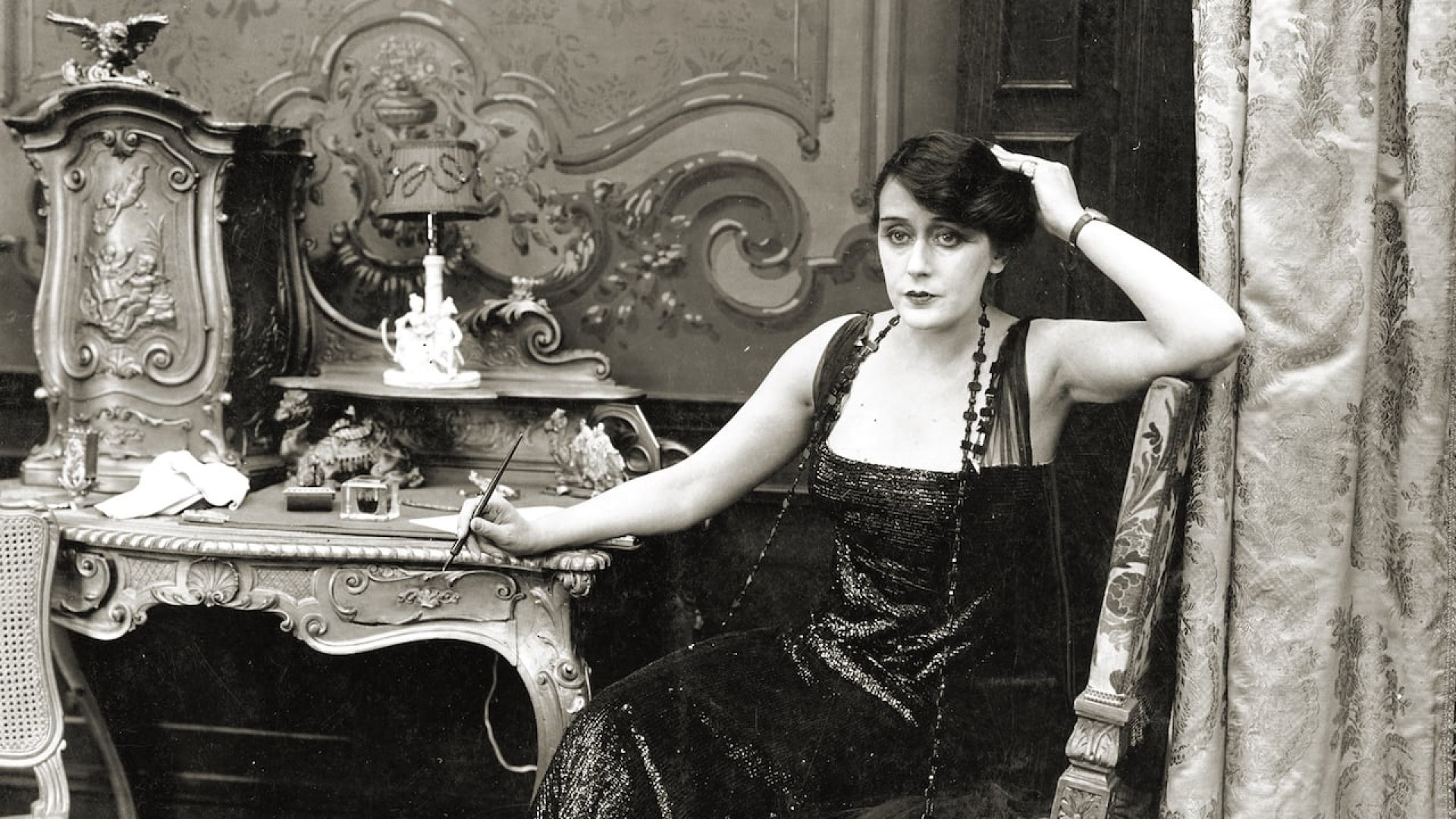 Alice Guy-Blaché sentada num quarto, com a mão apoiada na cabeça