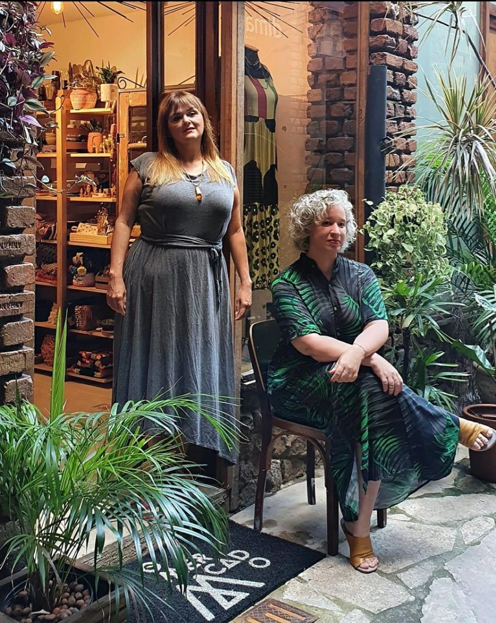 Duas mulheres posam na foto, uma sentada com braços cruzados e outra em pé