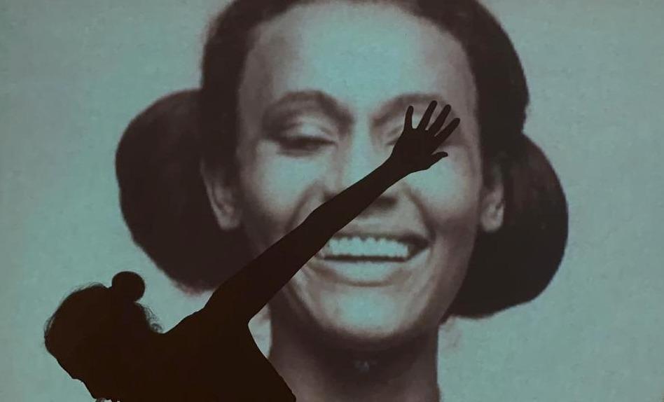 Camila Pitanga na frente de uma projeção na parede de foto da própria mãe